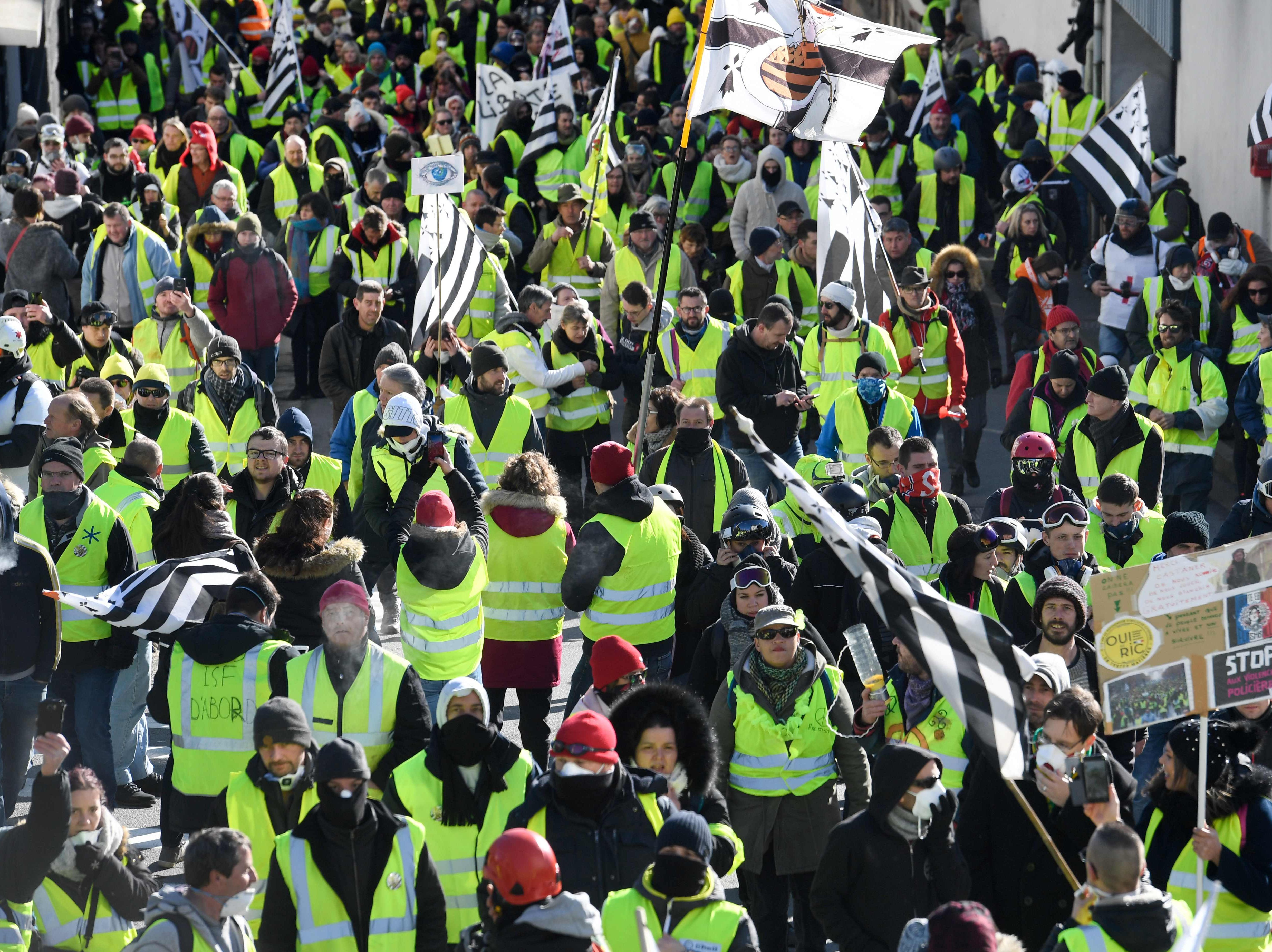 "Protesters take part in an anti-government demonstration called by the ""Yellow Vest""  movement and wave Brittany's regional flags in front of the sous-prefecture of Morlaix, Western France on Feb. 2, 2019."