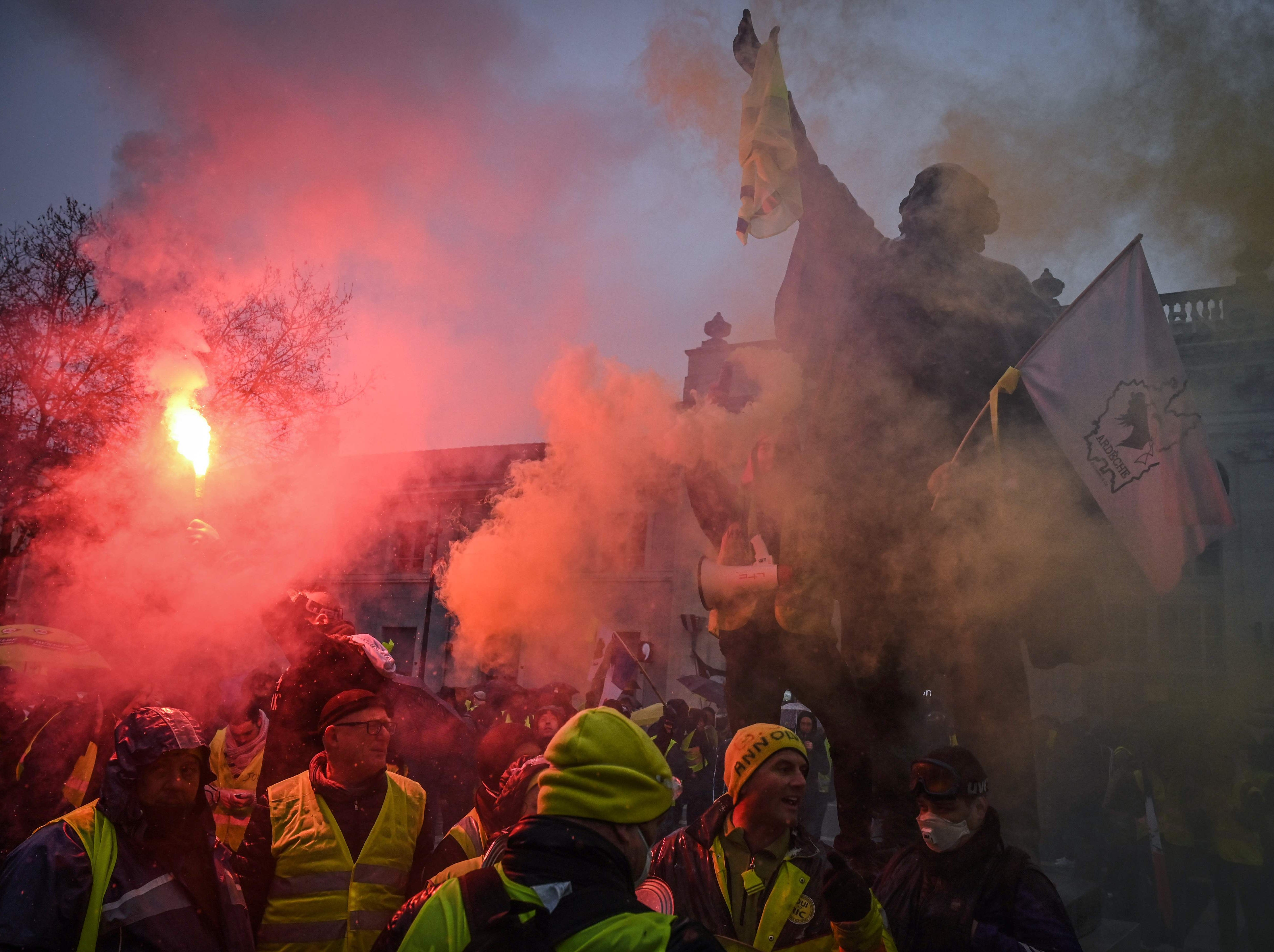 Protestors hold a red flare as they take in an anti-government demonstration called by the 'Yellow vests' movement in Valence, southeastern France, on Feb. 2, 2019.