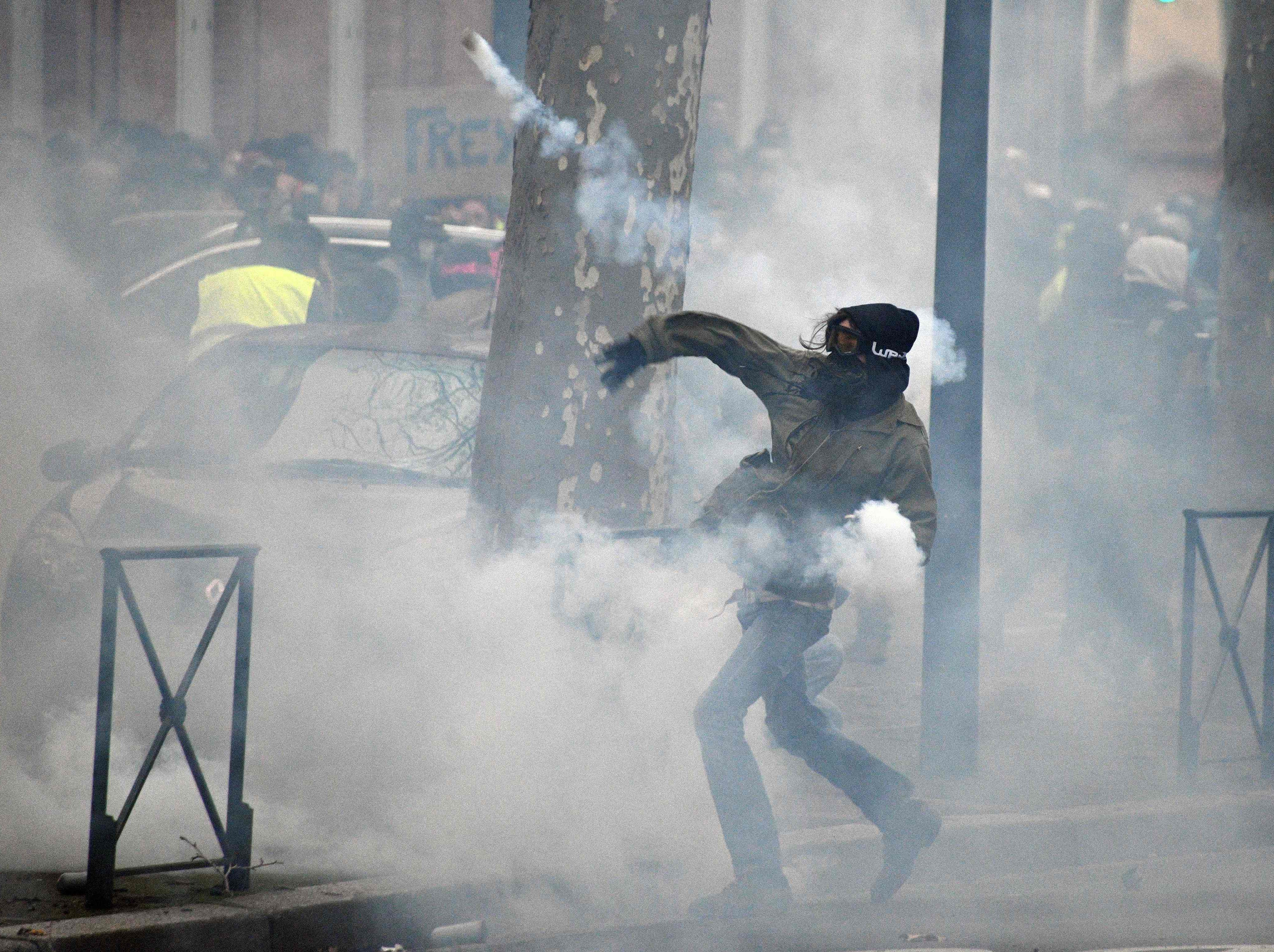 "A protester throws back a tear gas canister during an anti-government demonstration called by the ""Yellow Vest"" (Gilets Jaunes) movement on Feb. 2, 2019 in Toulouse. The 'Yellow Vest'  movement in France originally started as a protest about planned fuel hikes but has morphed into a mass protest against President's policies and top-down style of governing."