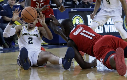 Rutgers forward Eugene Omoruyi (11) and Michigan guard Jordan Poole (2) chase the loose ball during the first half of an NCAA college basketball game, Sunday, Jan. 21, 2018, in Ann Arbor