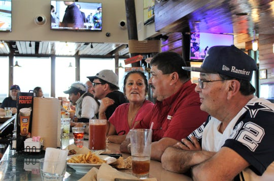 Gina Reibold talks football with Esa Ramirez, second from right, before Sunday's Super Bowl game. Reibold was at Hooters with her husband, Roger, fourth from right - they are truck drivers staying at a nearby hotel while their rig is being fixed. They joined Ramirez and his brother Johnny (82) at the bar for the game between the New England Patriots and Los Angeles Rams. The Reibolds are from California but are Dallas Cowboys fans, as is Johnny Ramirez.