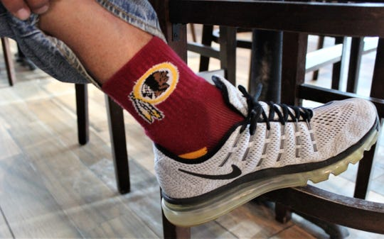 Esa Ramirez is a Washington Redskins fan, right down to the socks he wore Sunday to Hooters to watch the Super Bowl with his brother, Johnny - a Dallas Cowboys fan.