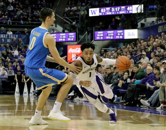 Washington guard David Crisp (1) drives around UCLA forward Alex Olesinski (0) during the second half of an NCAA college basketball game, Saturday, Feb. 2, 2019, in Seattle. Washington won 69-55. (AP Photo/Ted S. Warren)