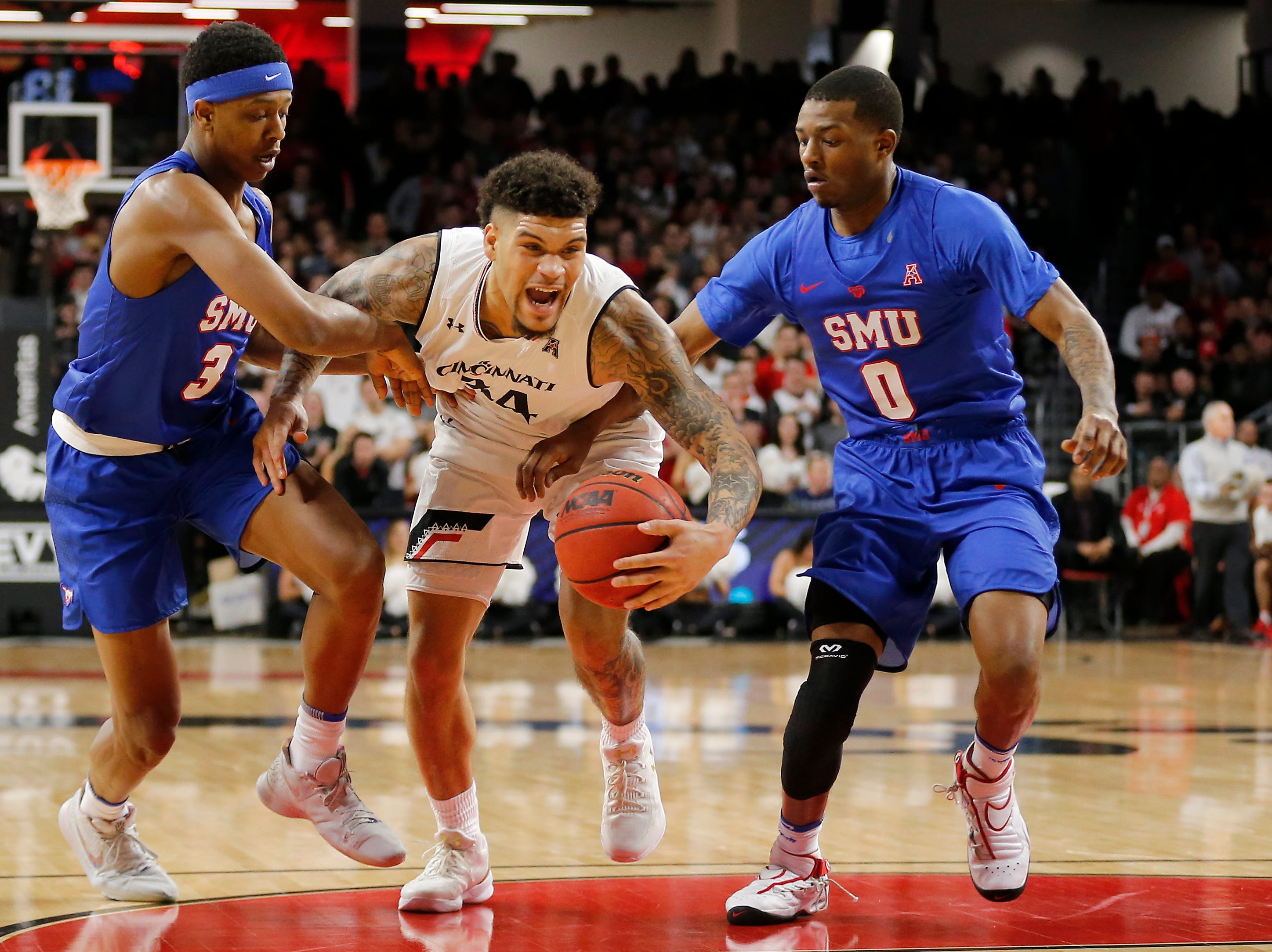 Cincinnati Bearcats guard Jarron Cumberland (34) drives into the paint against Southern Methodist Mustangs guard William Douglas (3) and guard Jahmal McMurray (0) in the first half the the NCAA American Athletic Conference basketball game between the Cincinnati Bearcats and the Southern Methodist Mustangs at Fifth Third Arena in Cincinnati on Saturday, Feb. 2, 2019.