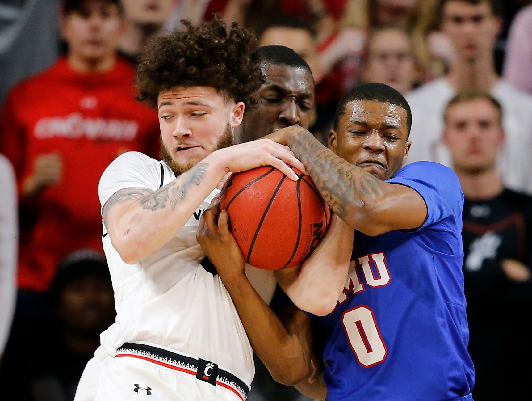 Cincinnati Bearcats guard Logan Johnson (0) wrestles with Southern Methodist Mustangs guard Jahmal McMurray (0) for the ball in the first half the the NCAA American Athletic Conference basketball game between the Cincinnati Bearcats and the Southern Methodist Mustangs at Fifth Third Arena in Cincinnati on Saturday, Feb. 2, 2019.