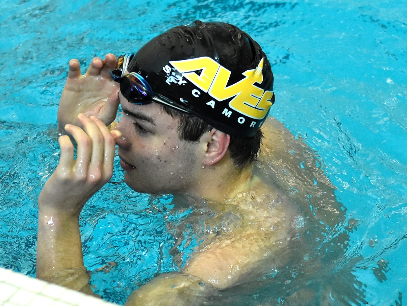 Sammy Risma removes the googles after securing the last leg to victory for Sycamore in the boys 200-yard individual medley at the 2019 Greater Miami Conference swimming championships, Feb. 2, 2019.