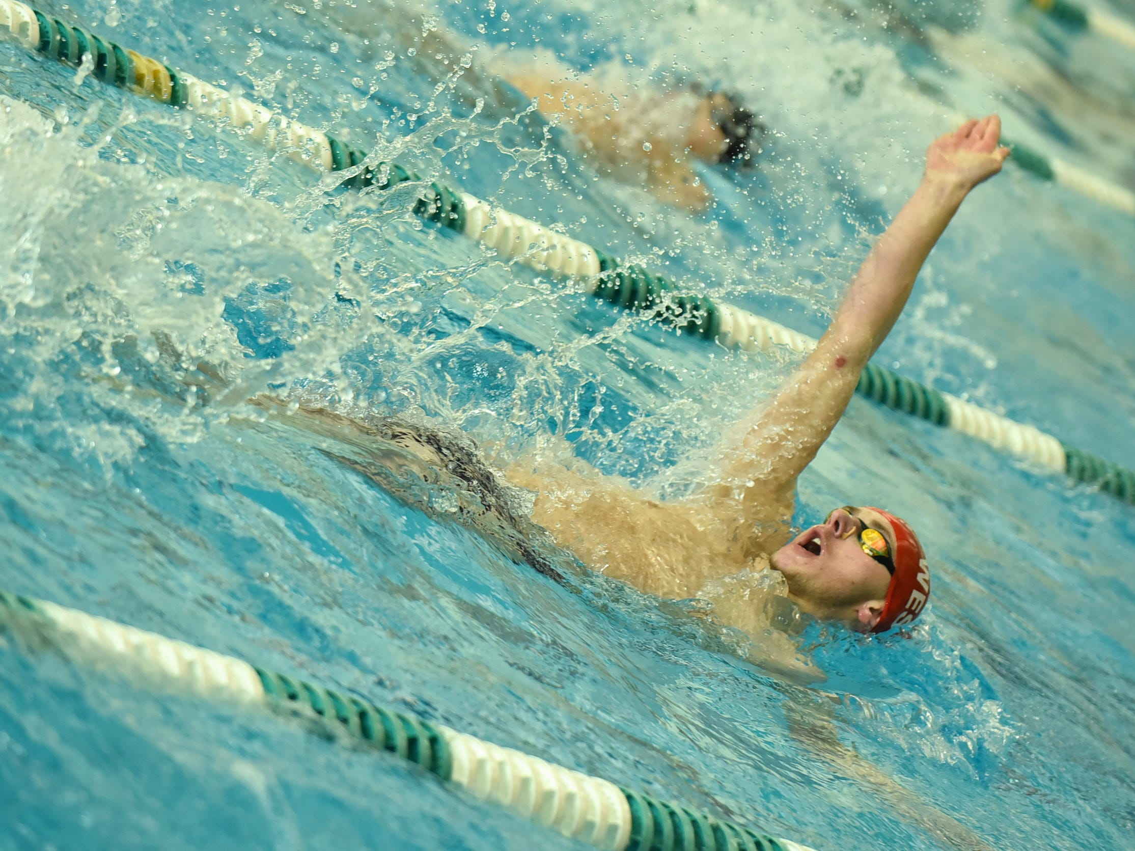 Michael Lorenz of Lakota West powers out the backstroke at the 2019 Greater Miami Conference swimming championships, Feb. 2, 2019.