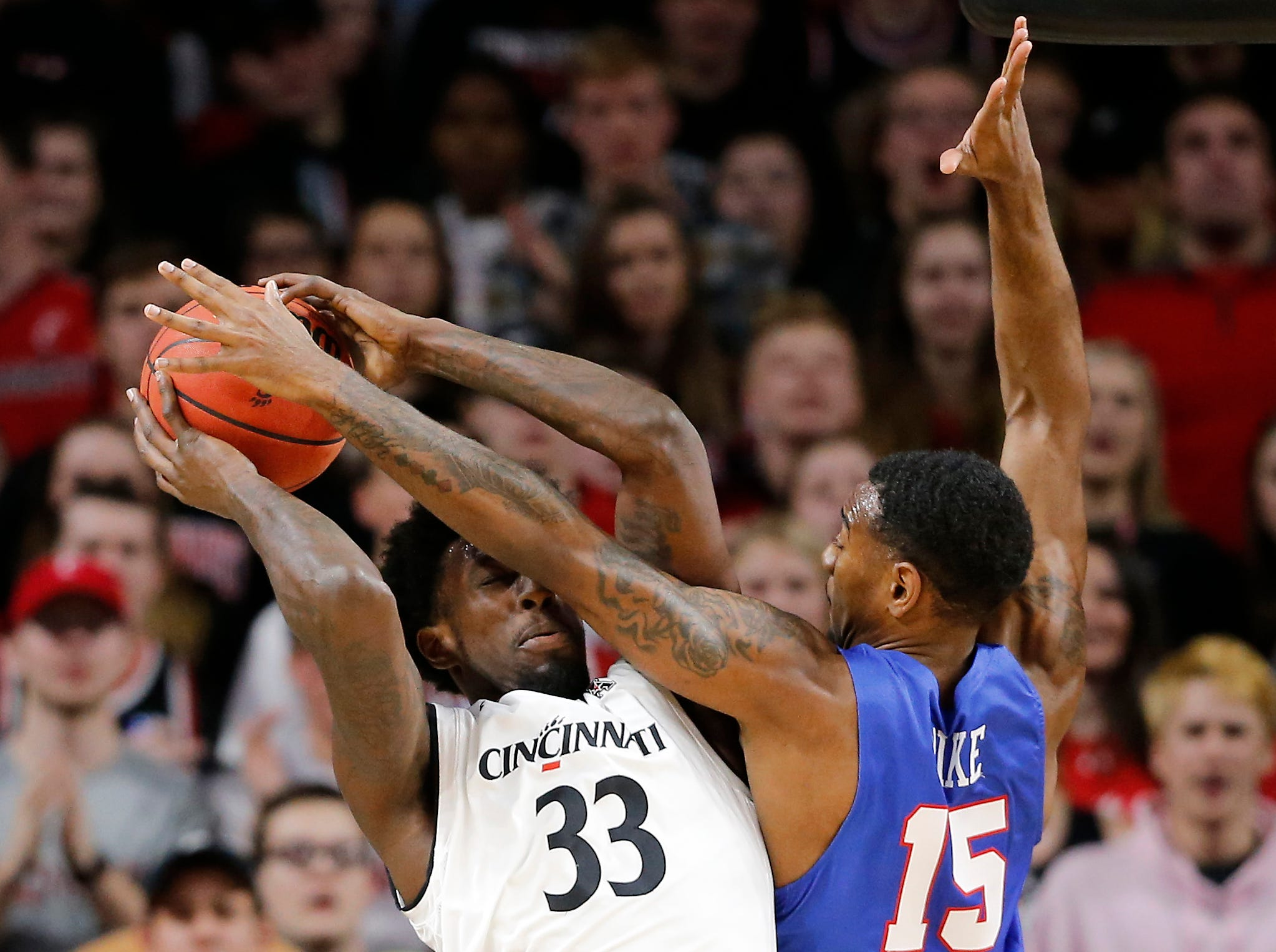 Cincinnati Bearcats center Nysier Brooks (33) pulls down a rebound over Southern Methodist Mustangs forward Isiaha Mike (15) in the first half the the NCAA American Athletic Conference basketball game between the Cincinnati Bearcats and the Southern Methodist Mustangs at Fifth Third Arena in Cincinnati on Saturday, Feb. 2, 2019.
