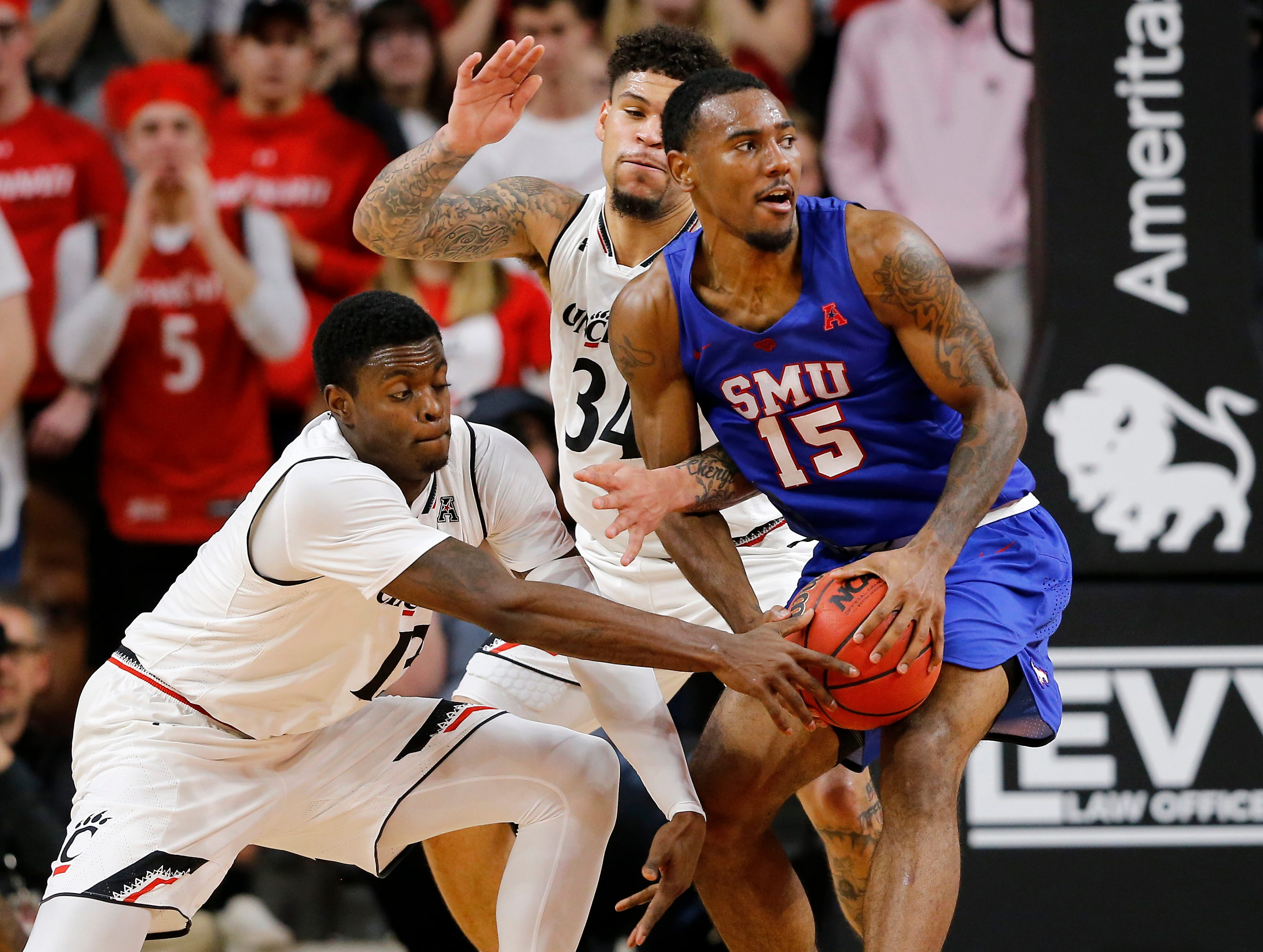 Cincinnati Bearcats forward Tre Scott (13) reaches in as Southern Methodist Mustangs forward Isiaha Mike (15) tries to pass in the first half the the NCAA American Athletic Conference basketball game between the Cincinnati Bearcats and the Southern Methodist Mustangs at Fifth Third Arena in Cincinnati on Saturday, Feb. 2, 2019.