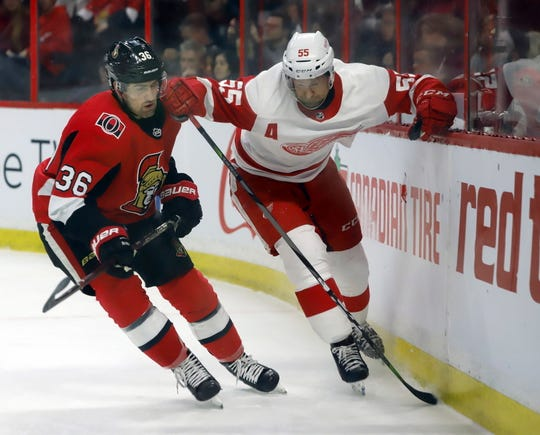 The Senators' Colin White and Red Wings defenseman Niklas Kronwall race for possession of the puck during the second period of the Red Wings' 2-0 win on Saturday, Feb. 2, 2019, in Ottawa.