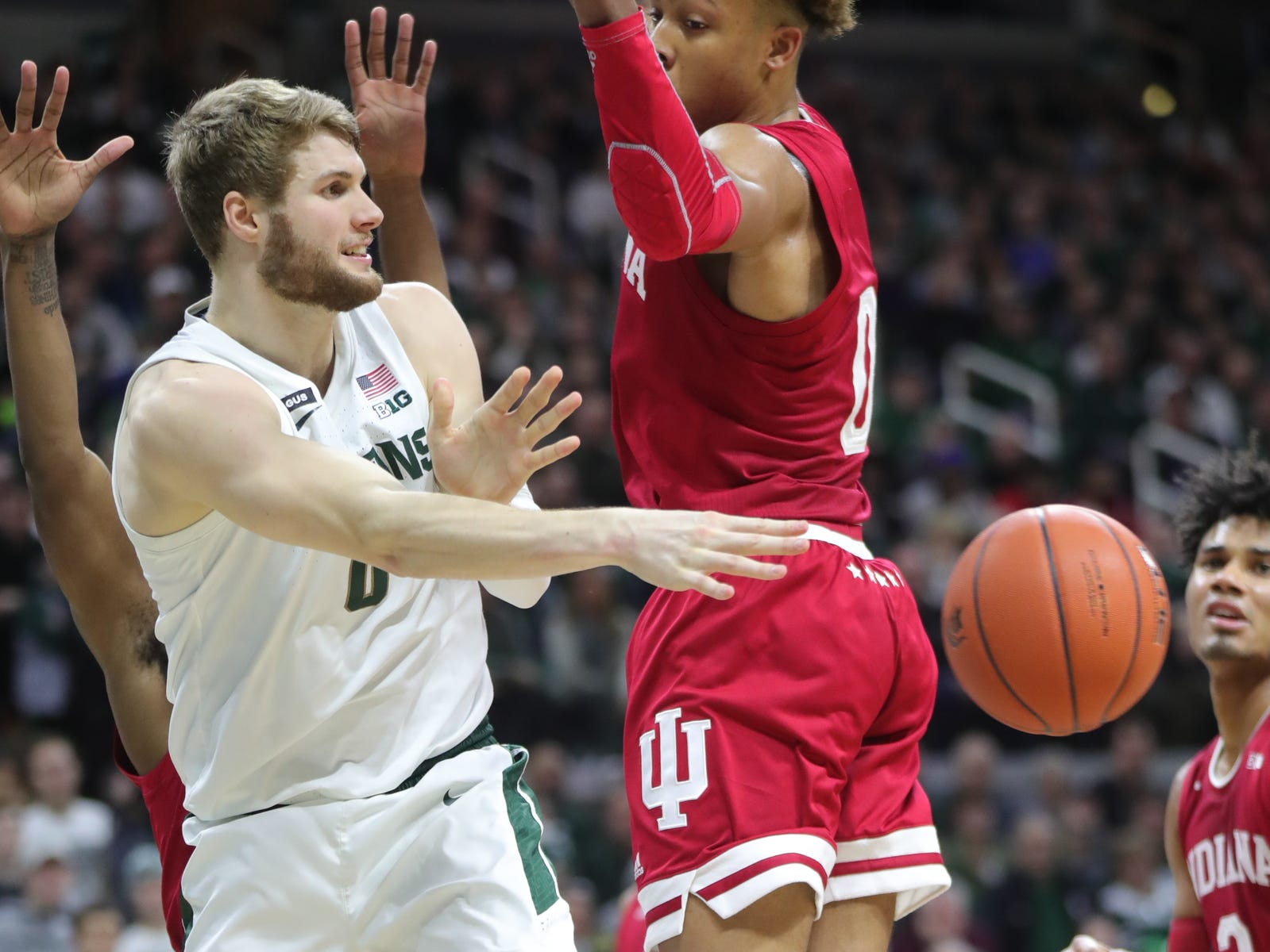 Michigan State forward Kyle Ahrens  passes against Indiana guard Romeo Langford during first half action Saturday, Feb. 2, 2019 at the Breslin Center in East Lansing, Mich.