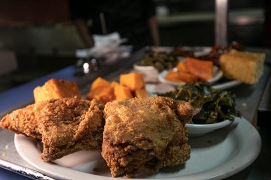 Golden crispy fried chicken is served up with candied yams and collard greens at Bert's Entertainment Complex in Eastern Market Friday, Jan. 25, 2019.
