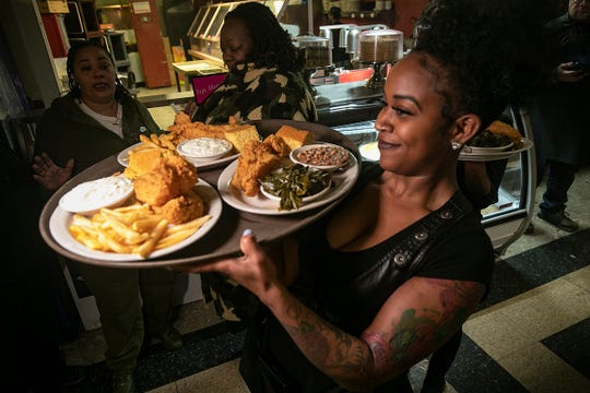 Waitress Maya Johnson of Detroit carries a tray of food that includes soul food favorites fried chicken, black eyed peas and collard greens Friday, Jan. 25, 2019 at Bert's Entertainment Complex.