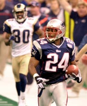 New England Patriots cornerback Ty Law (24) is trailed by St. Louis Rams' Isaac Bruce (80) as he scores a touchdown during the second quarter of Super Bowl XXXVI.