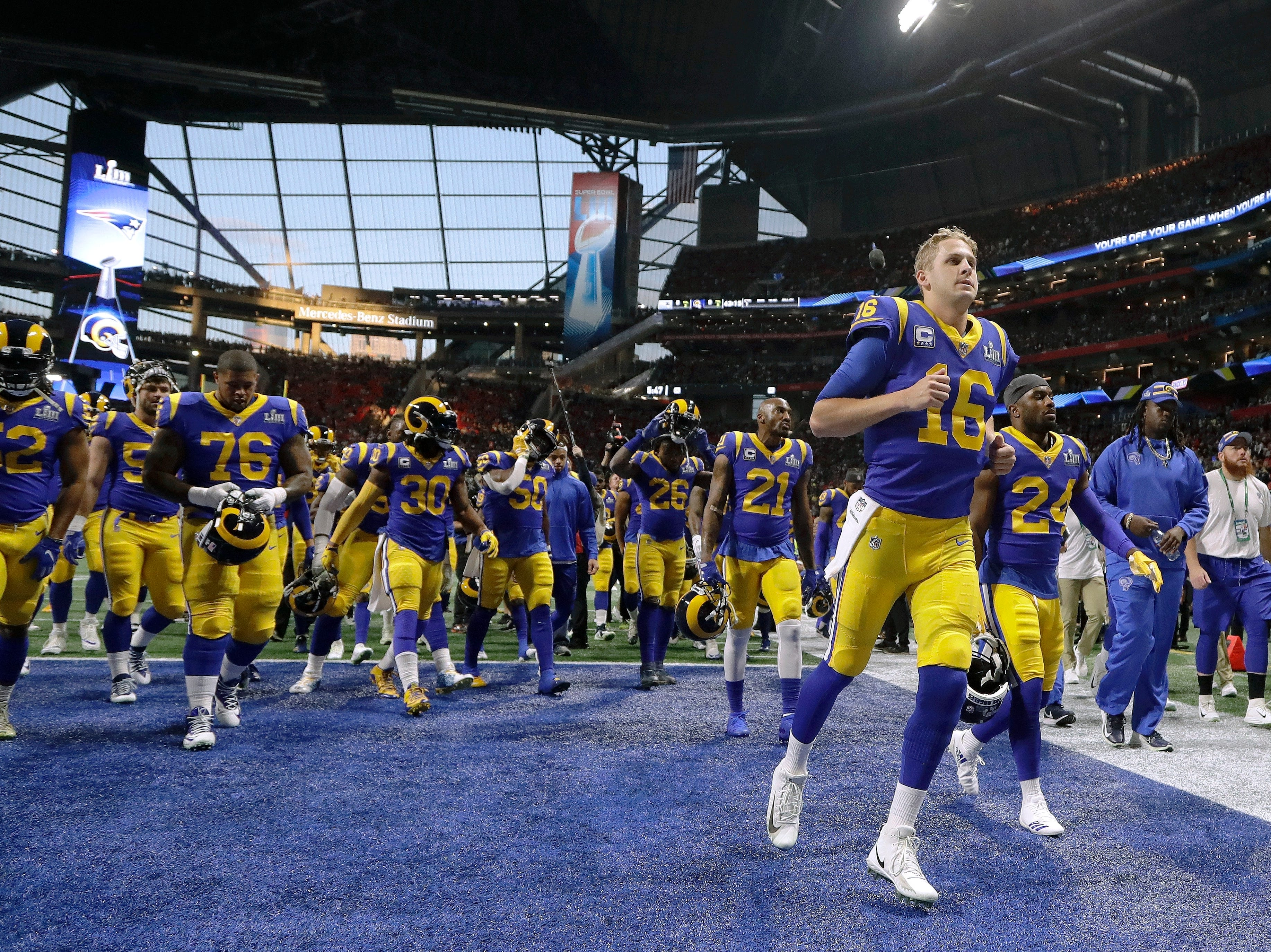 Los Angeles Rams' Jared Goff (16) runs to the locker room with his teammates before the game.