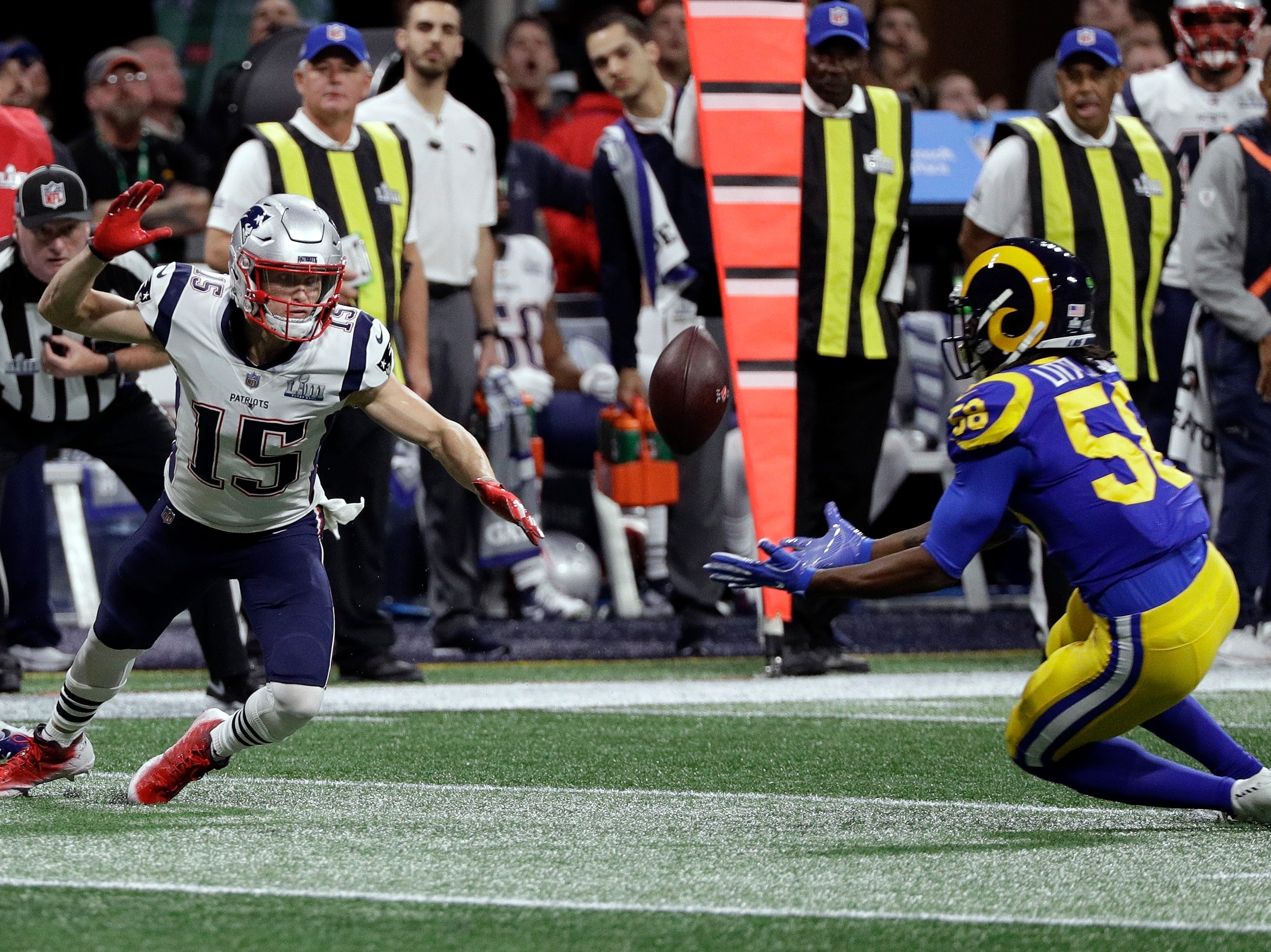 Los Angeles Rams' Cory Littleton, right, intercepts a pass intended for New England Patriots' Chris Hogan, left, during the first half.