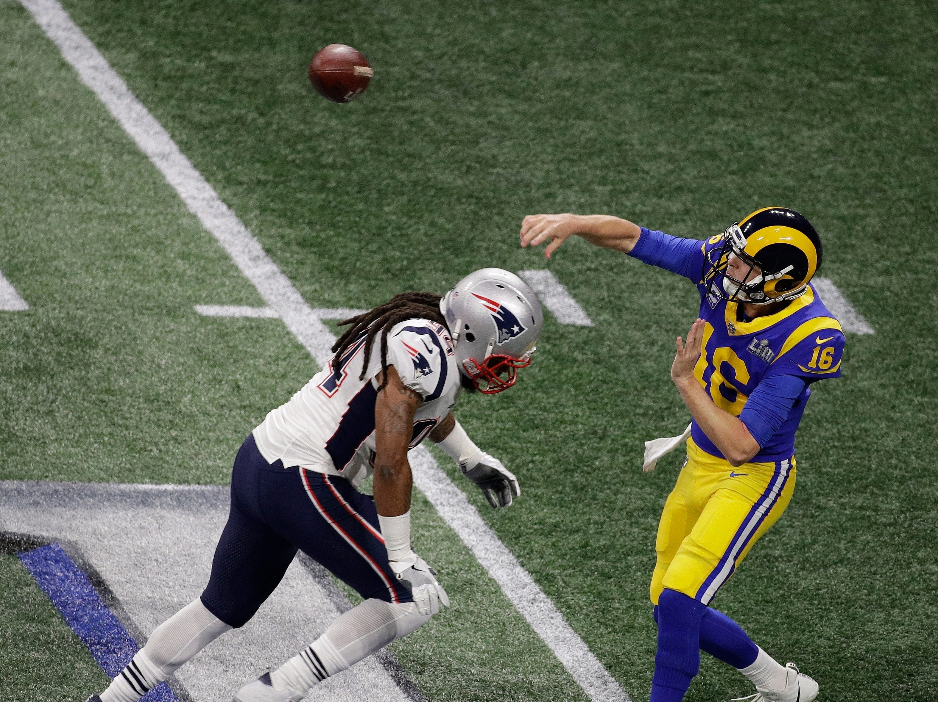 Los Angeles Rams' Jared Goff (16) works under pressure from New England Patriots' Adrian Clayborn (94) during the first half.