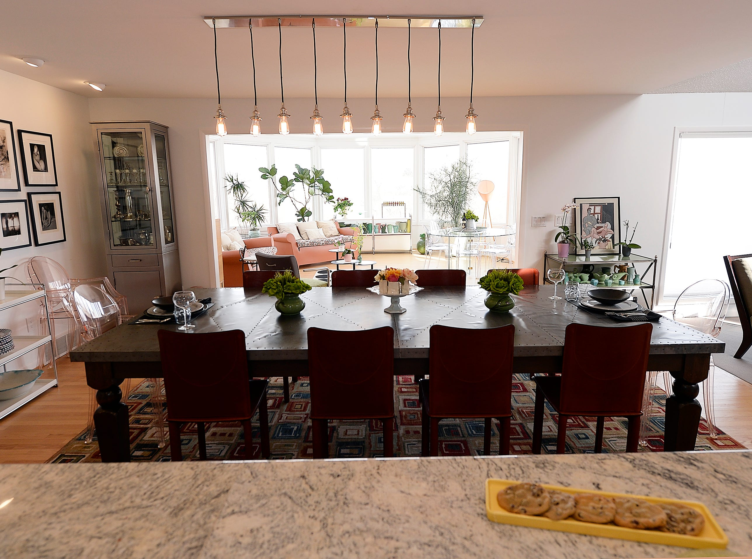 A long table sits in the dining room with a view of the open conservatory room.