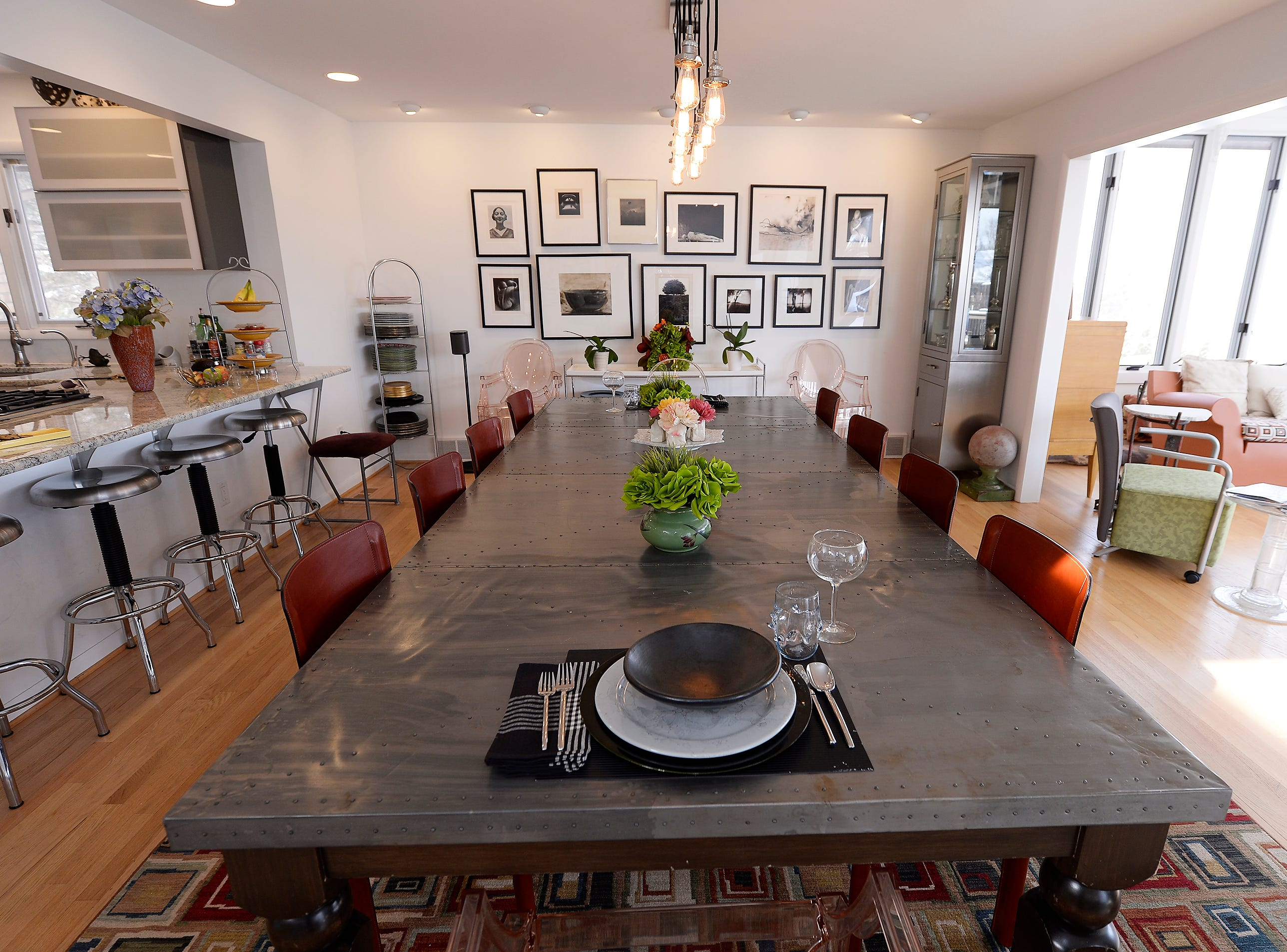A long table sits in the dining room with a black & white photo wall in the background.
