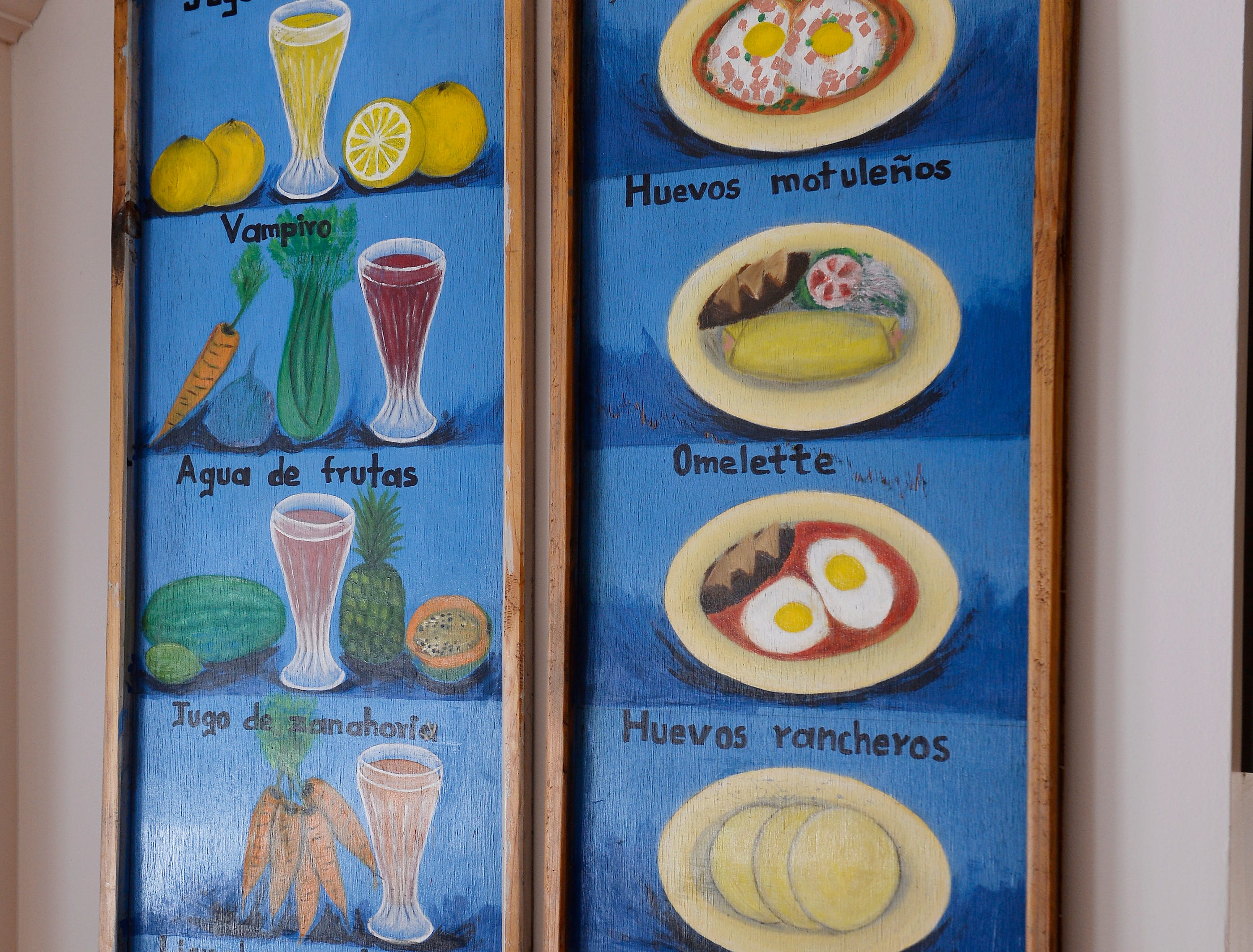 A  wood restaurant menu from Mexico is on display in the kitchen.