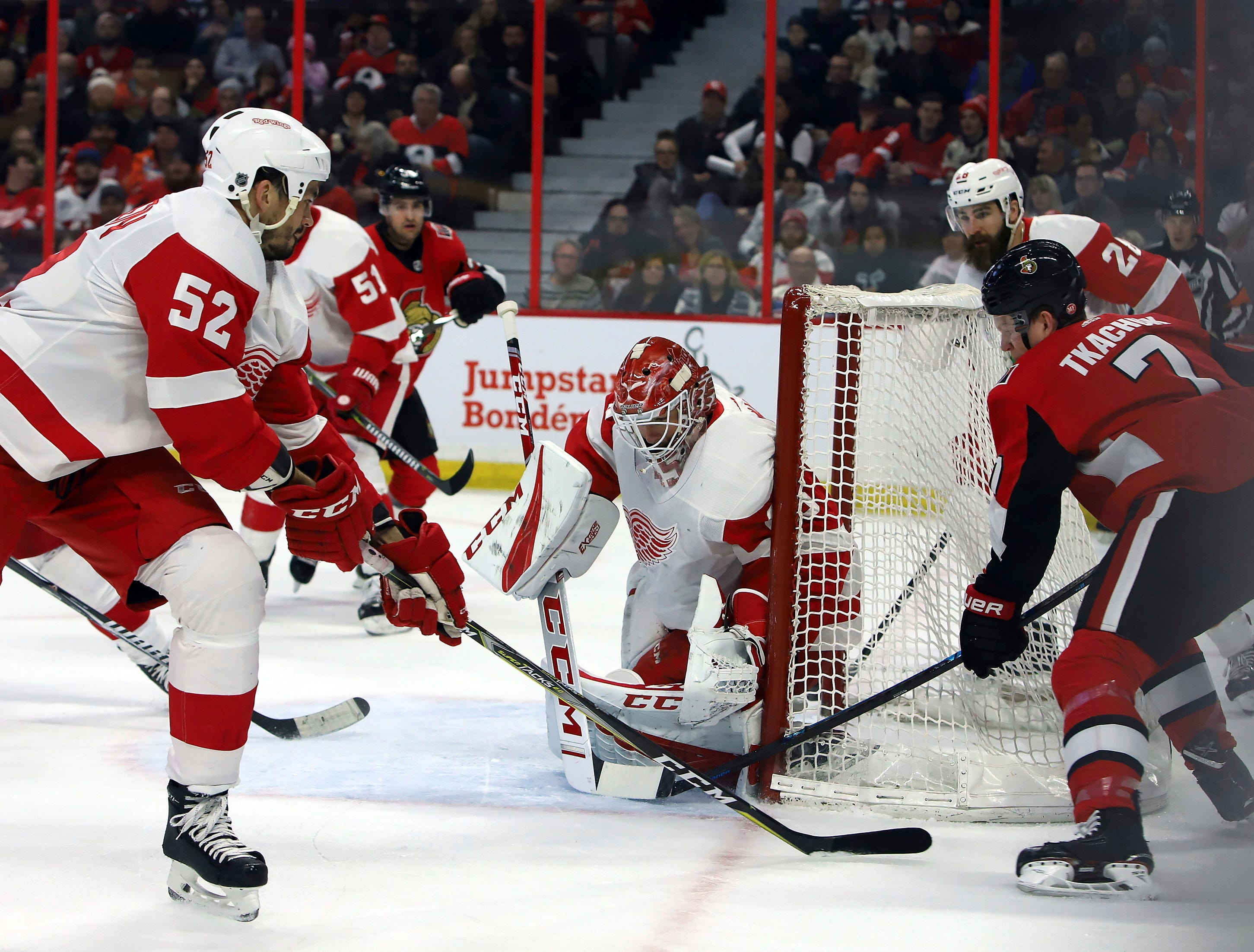 Detroit Red Wings' Jonathan Ericsson (52) defends as goaltender Jonathan Bernier (45) blocks a wraparound attempt by Ottawa Senators' Brady Tkachuk (7) during second-period NHL hockey game action in Ottawa, Saturday, Feb. 2, 2019. (Fred Chartrand/The Canadian Press via AP)