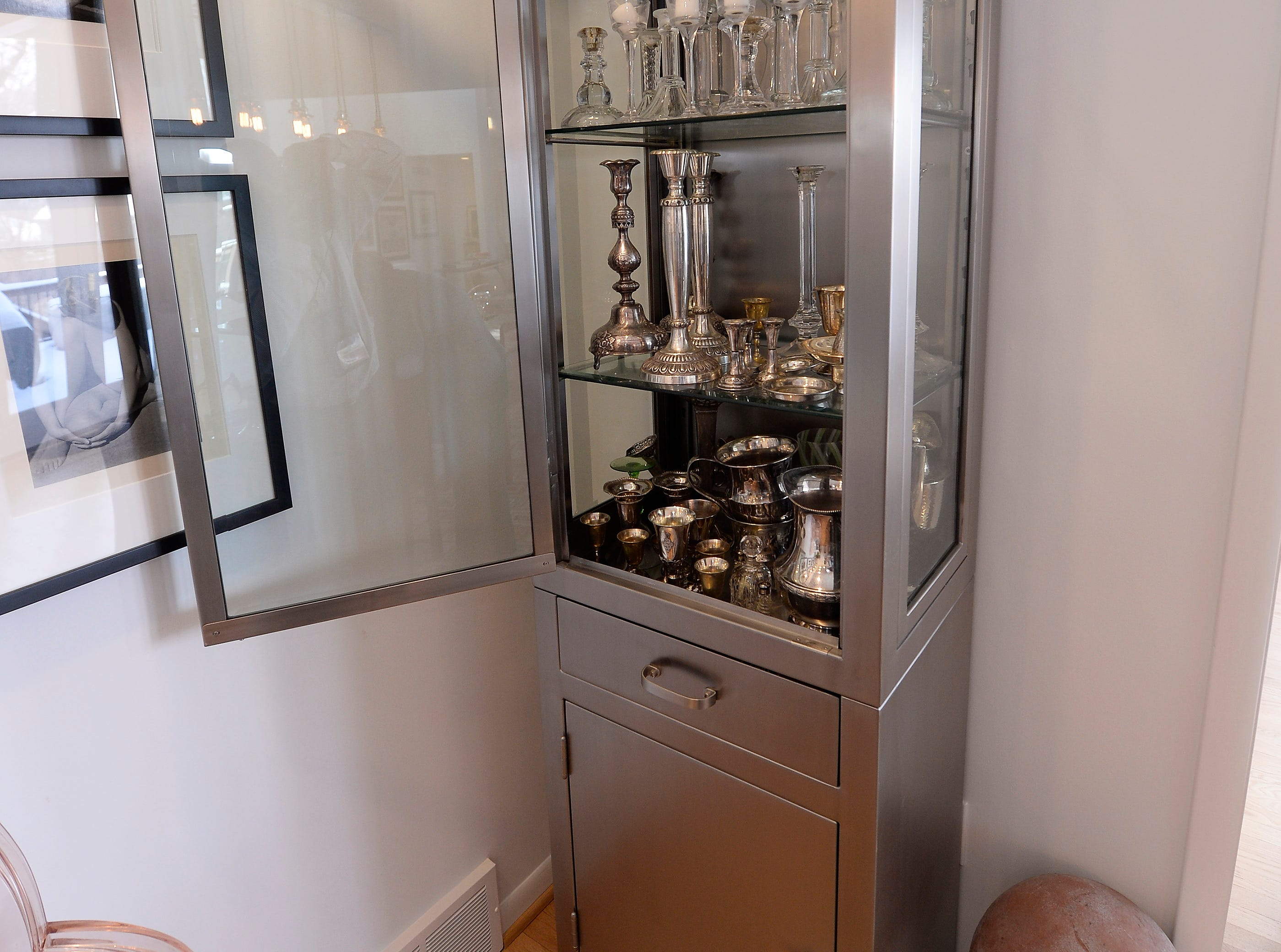 A steel cabinet with antique silver sits in the dining room.