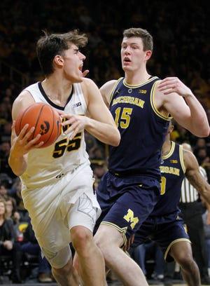Forward Luka Garza of the Iowa Hawkeyes goes under the basket in the second half against center Jon Teske of the Michigan Wolverines.