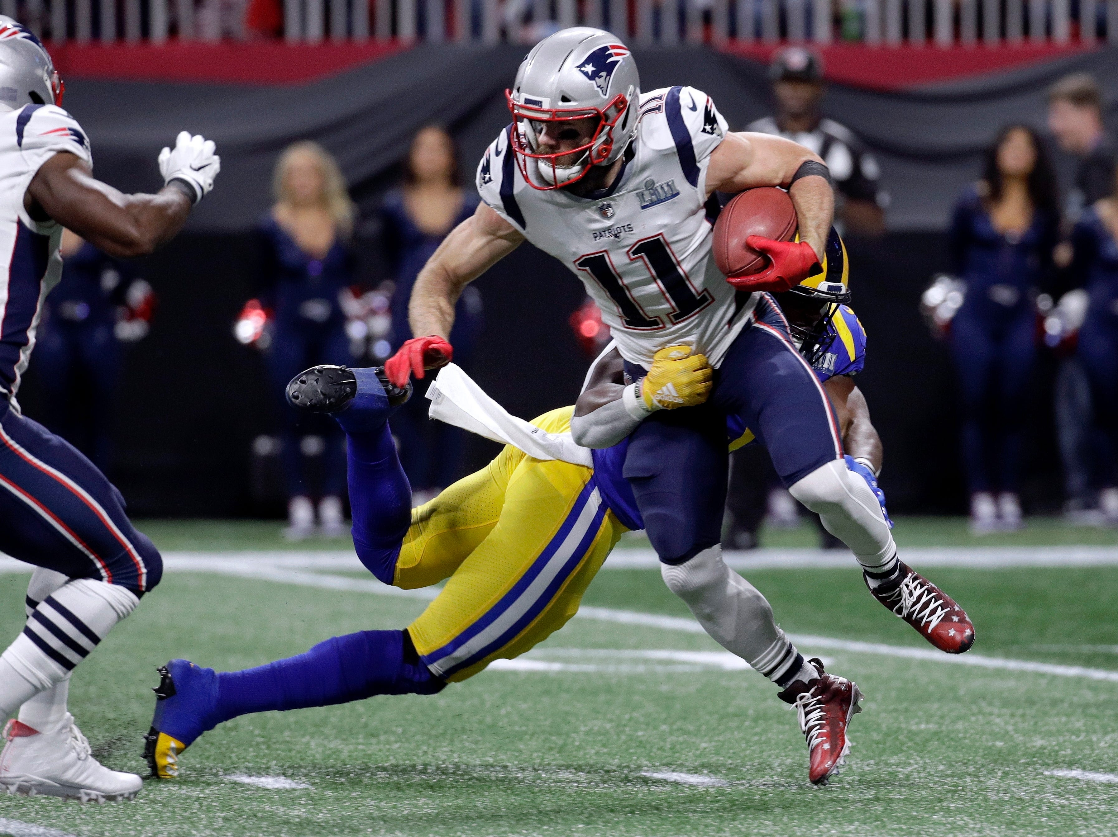 New England Patriots' Julian Edelman (11) is tackled by Los Angeles Rams' Samson Ebukam, rear, during the first half.