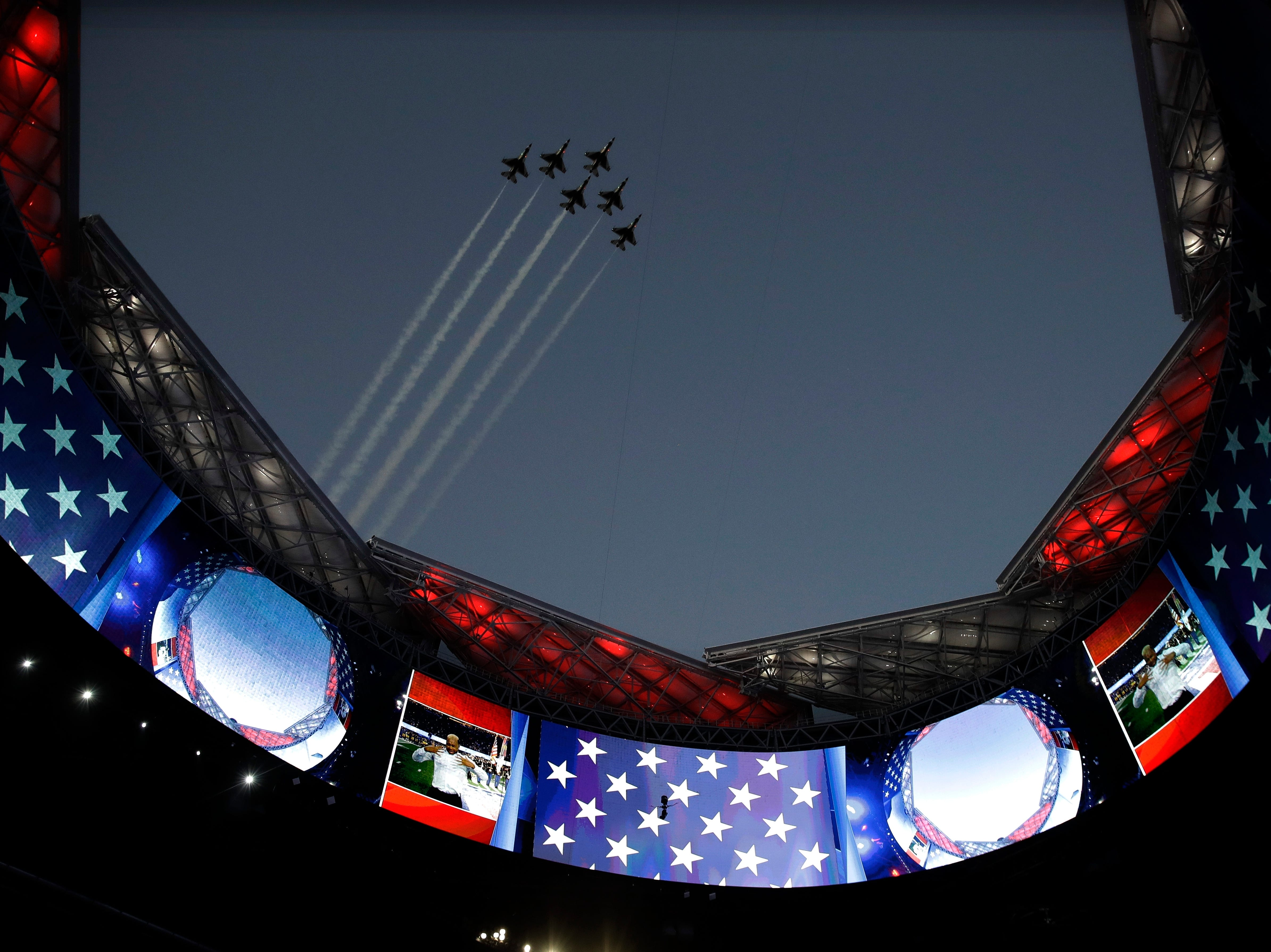 U.S. Air Force Thunderbirds fly over the open roof of the Mercedes-Benz Stadium before the game.