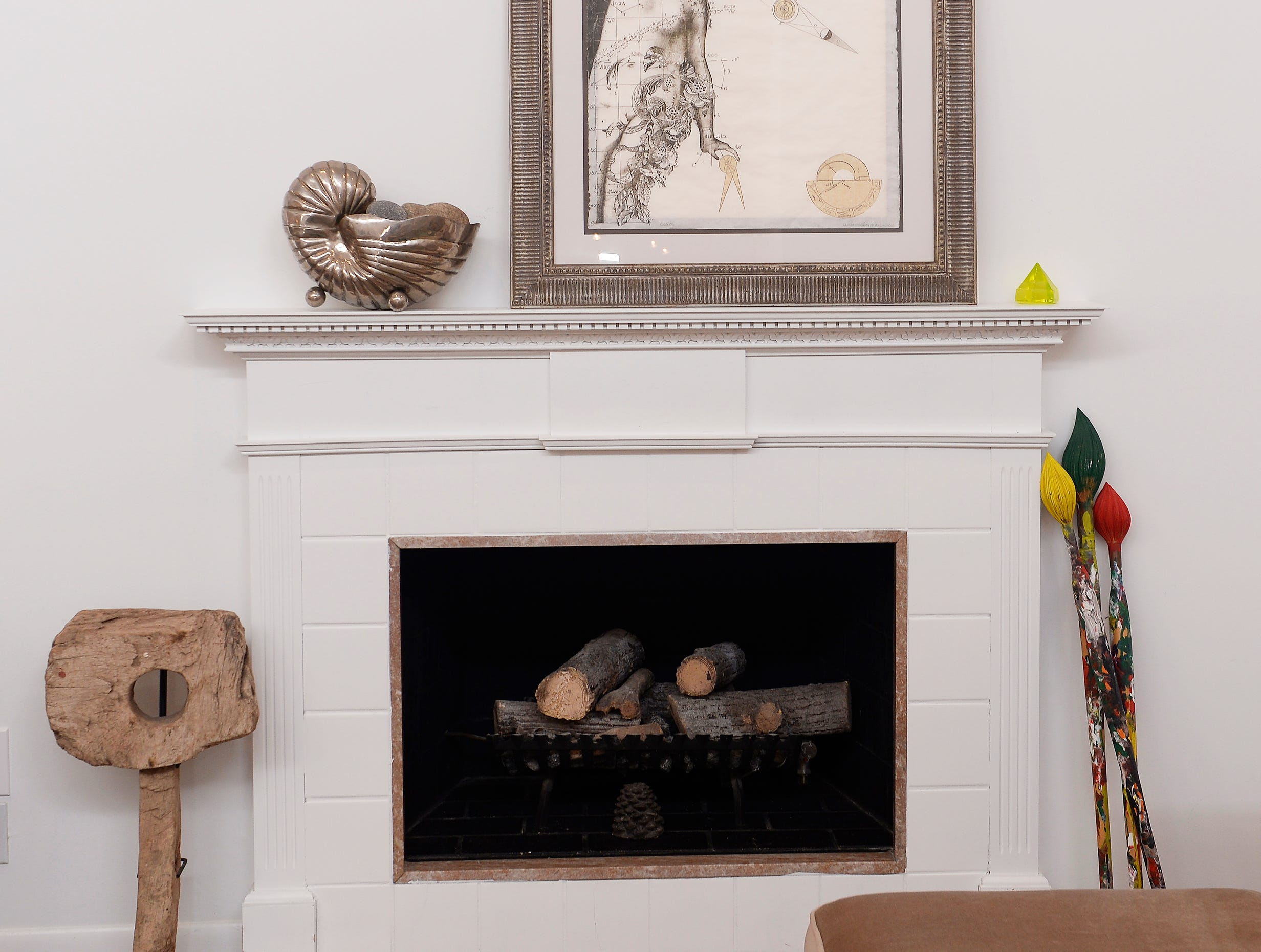 The fireplace with wood paint brushes inside the living room.