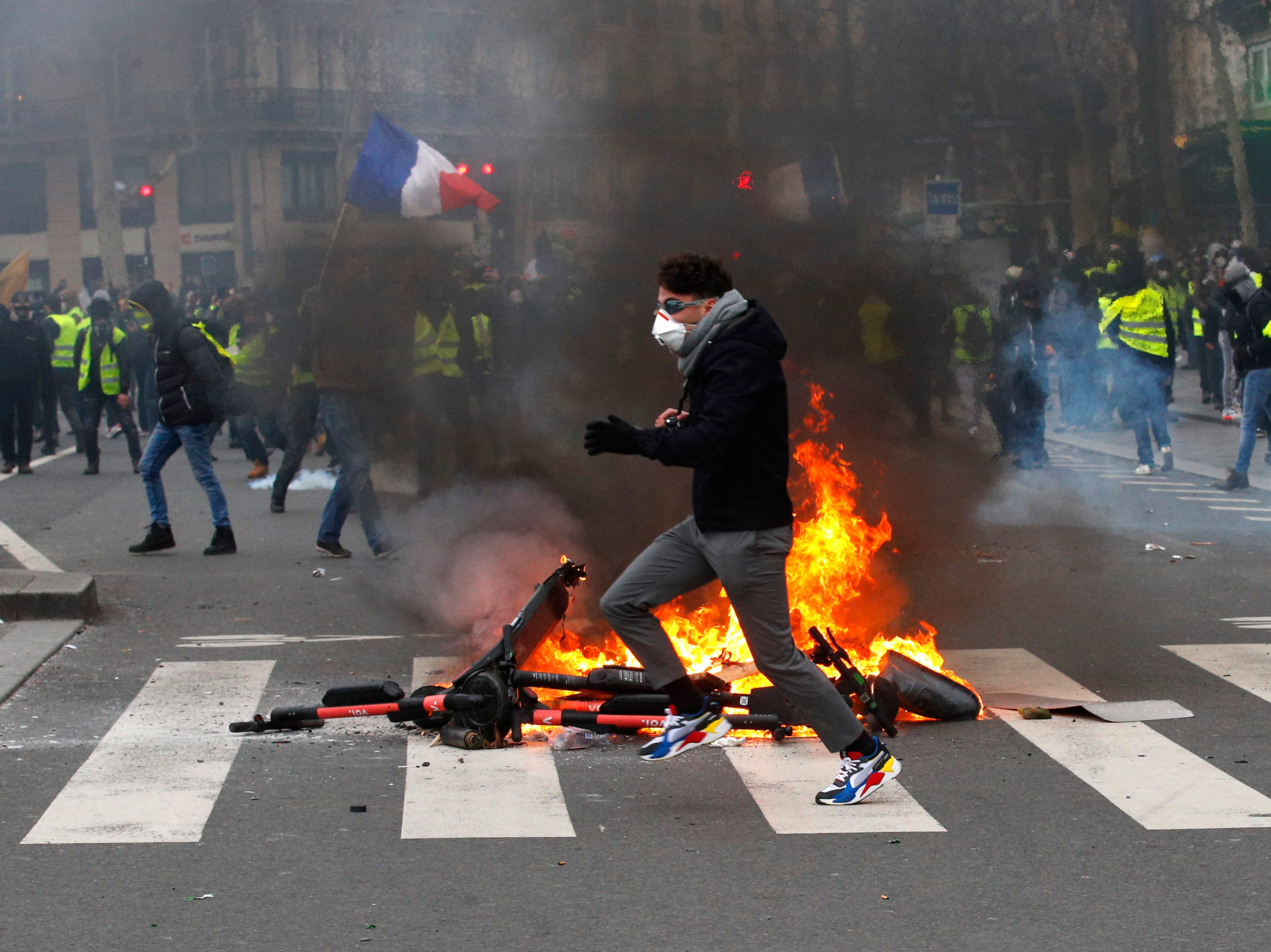 A demonstrator runs by a fire during a yellow vest protest Saturday, Feb. 2, 2019 in Paris. France's yellow vest protesters are taking to the streets to keep pressure on French President Emmanuel Macron's government, for the 12th straight weekend of demonstrations. This week, demonstrators in the French capital are planning to pay tribute to the yellow vests injured during clashes with police.