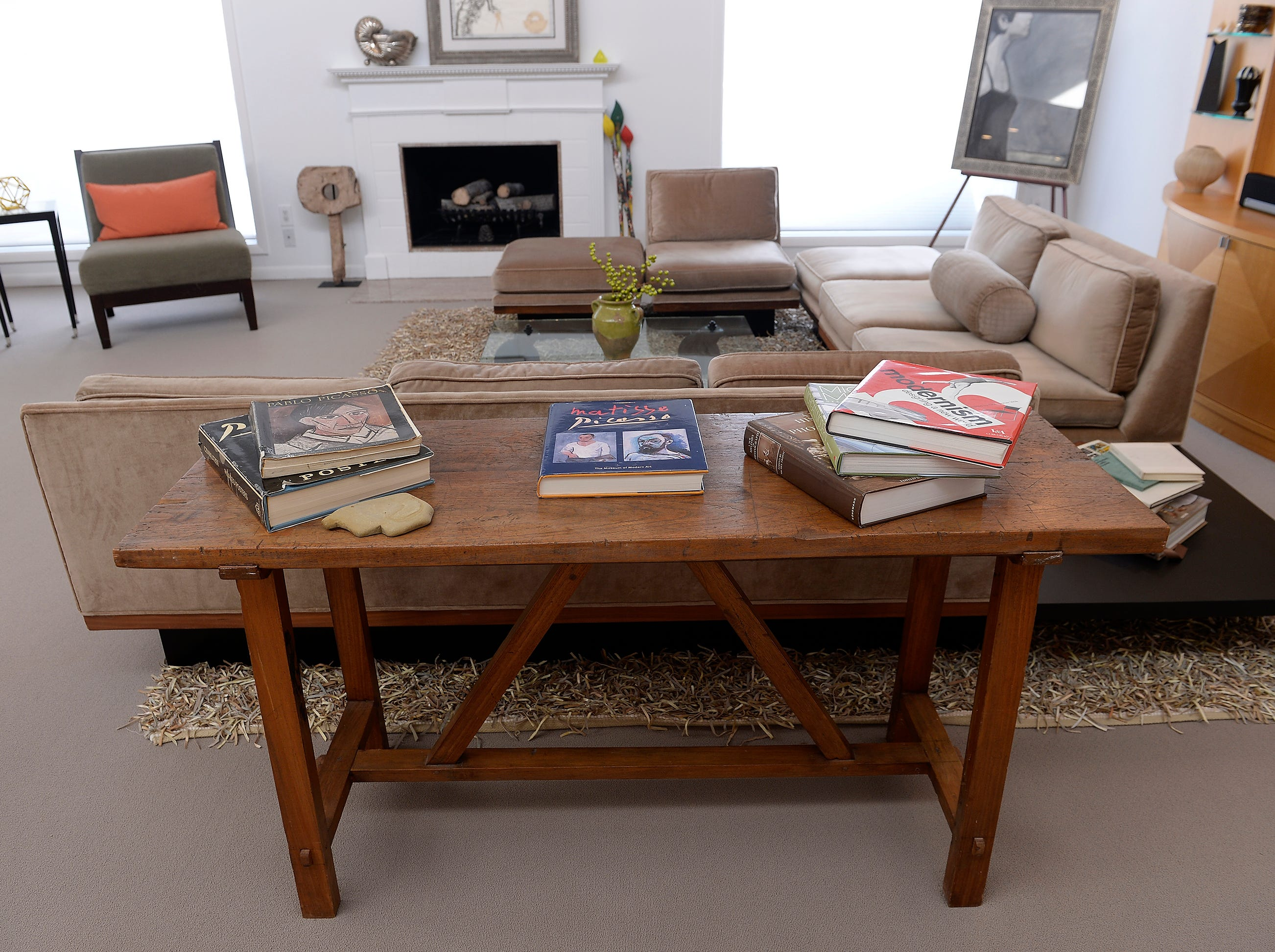 A wood table with art books inside the living room.