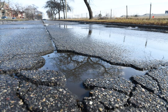 Water fills a pothole on the I-94 service drive near John R in Detroit Sunday.