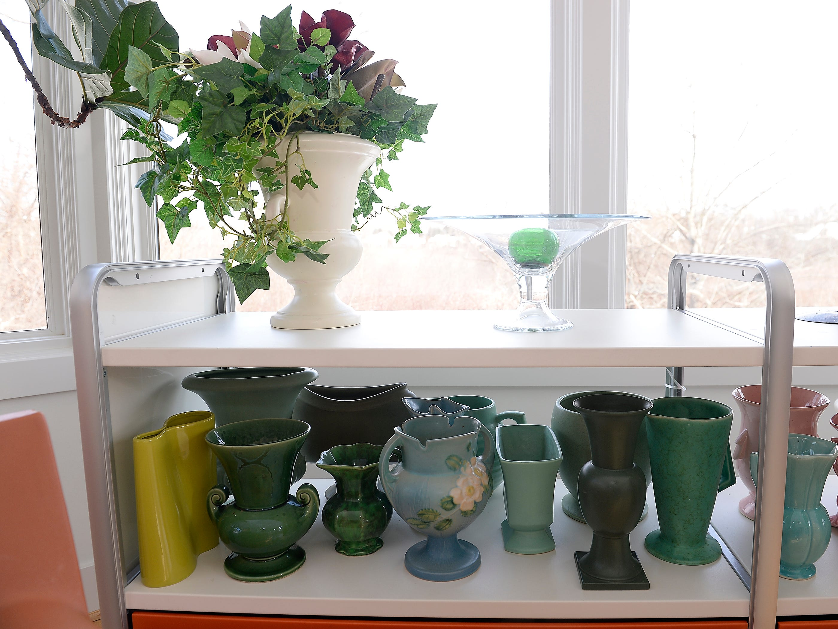 Mid-Century pottery sits on a window shelf inside the conservatory room.