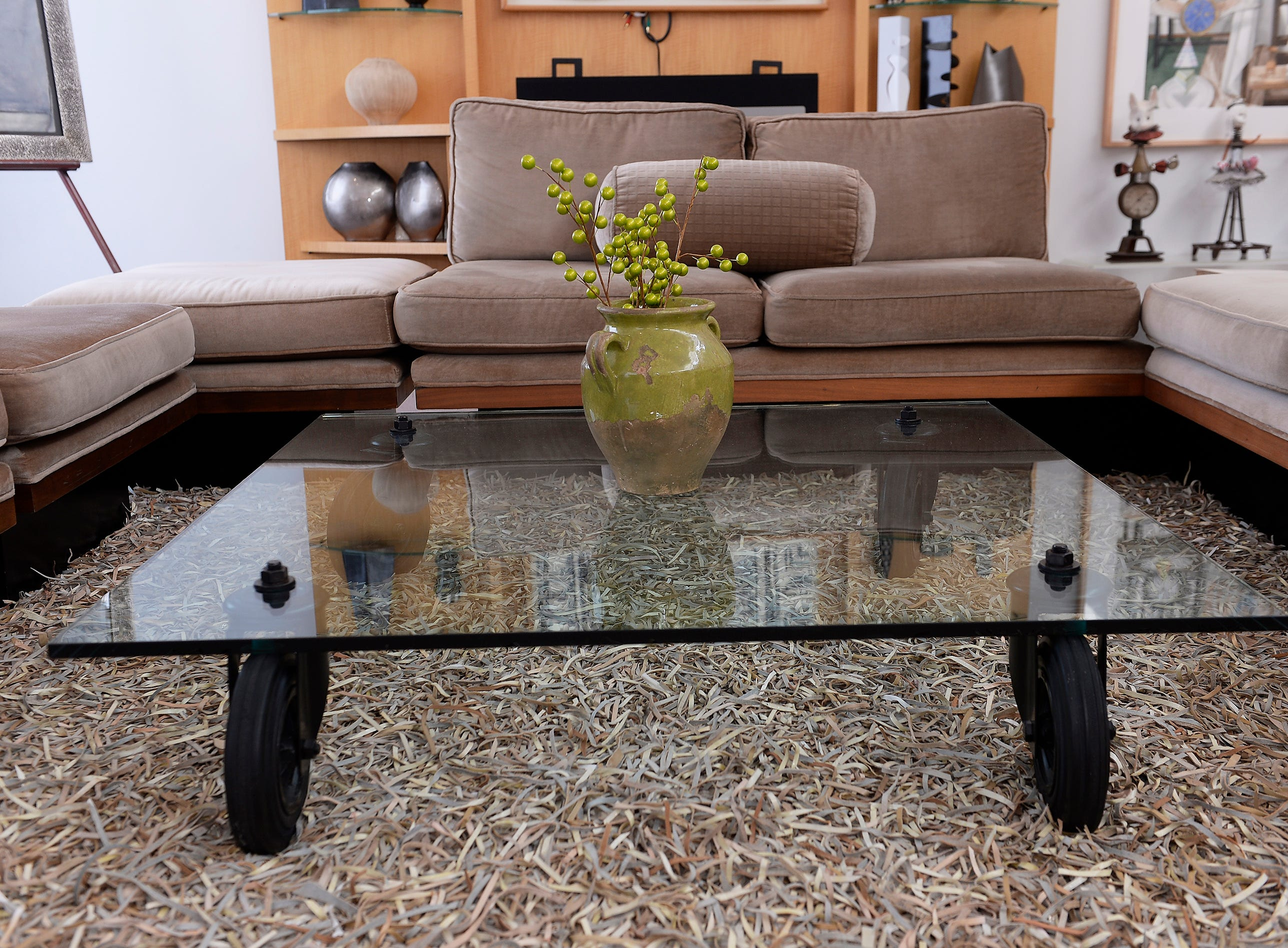 A glass table with a milo baughman sofa sits inside the living room.