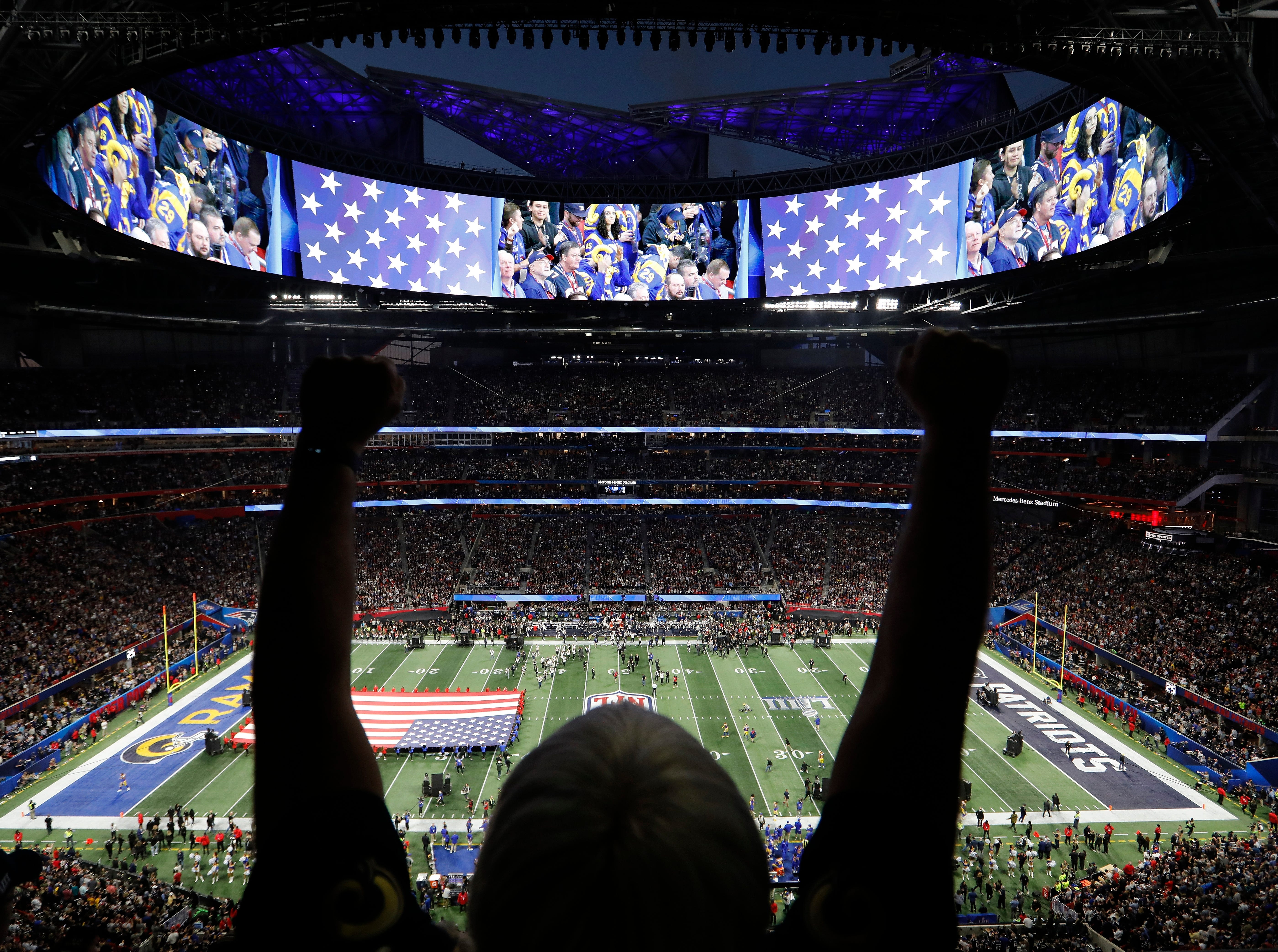A fan watches the national anthem before the first half.