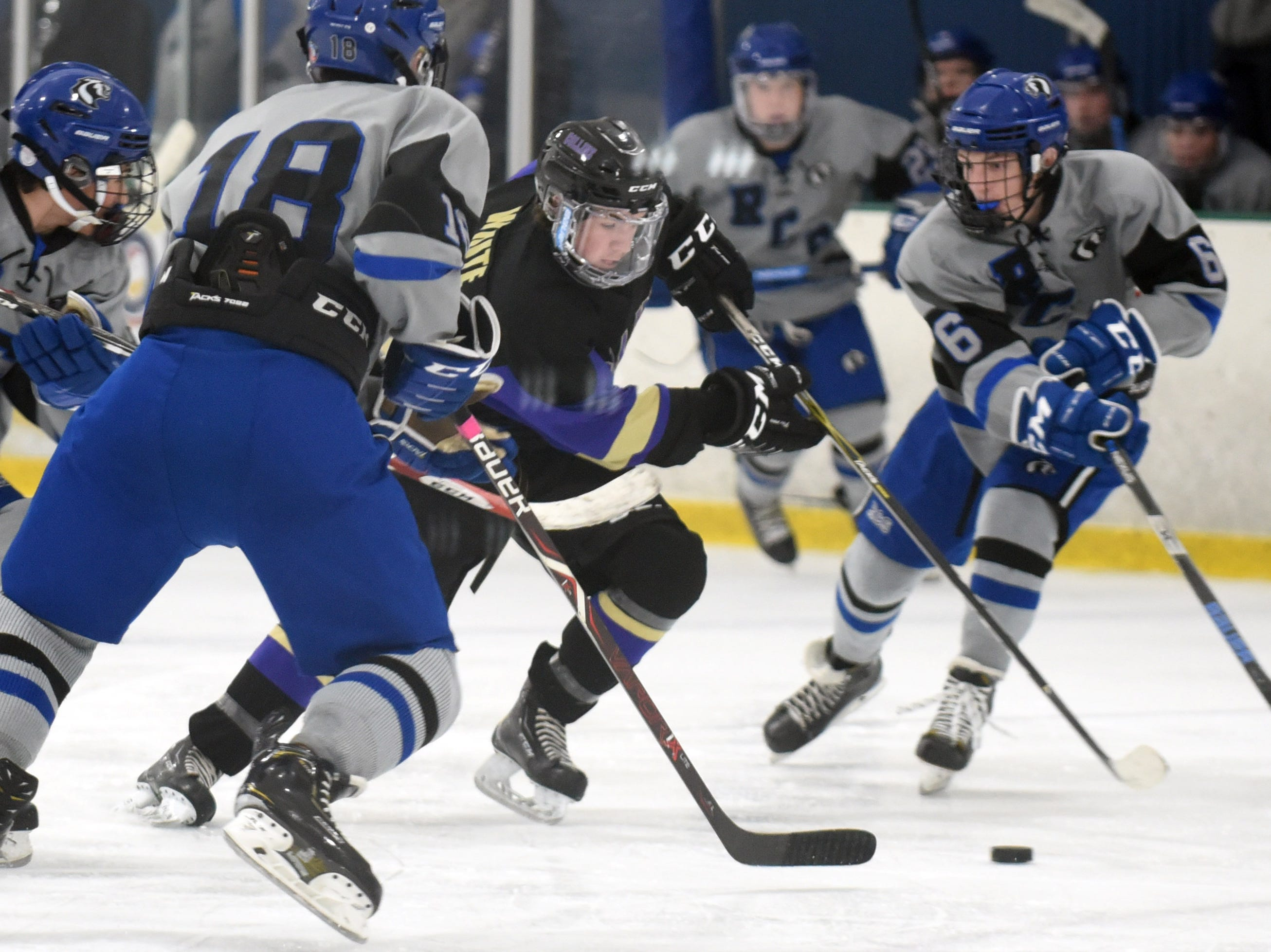 Fort Collins' Denny White tries to break through Resurrection Christian's defenders Perry McIntire and Jake Little during the game on Saturday, Feb 2, at NoCo Ice Center, 7900 N Fairgrounds Ave, in Fort Collins.