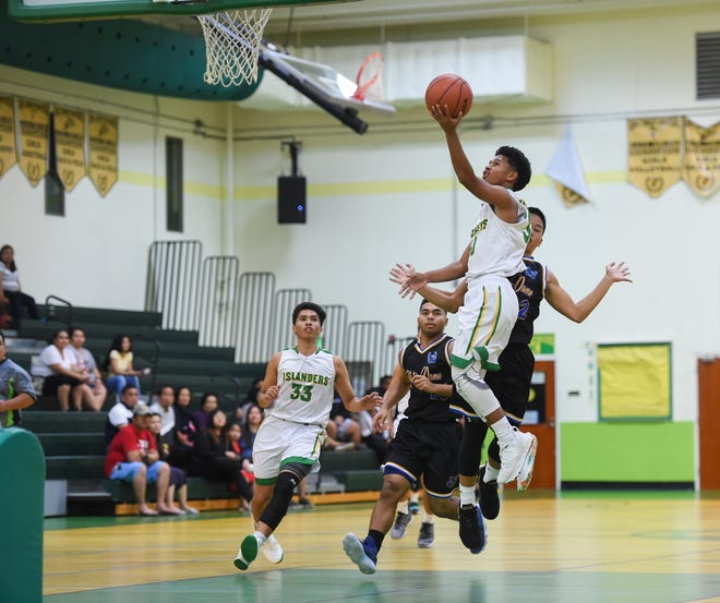 In this Feb. 2 file photo, Jeremiah Kintoki drives to the basket for the John F. Kennedy Islanders during an IIAAG Boys Basketball game against the Notre Dame Royals. Kintoki led JFK to a 59-55 win over the Okkodo High School Bulldogs on Tuesday.