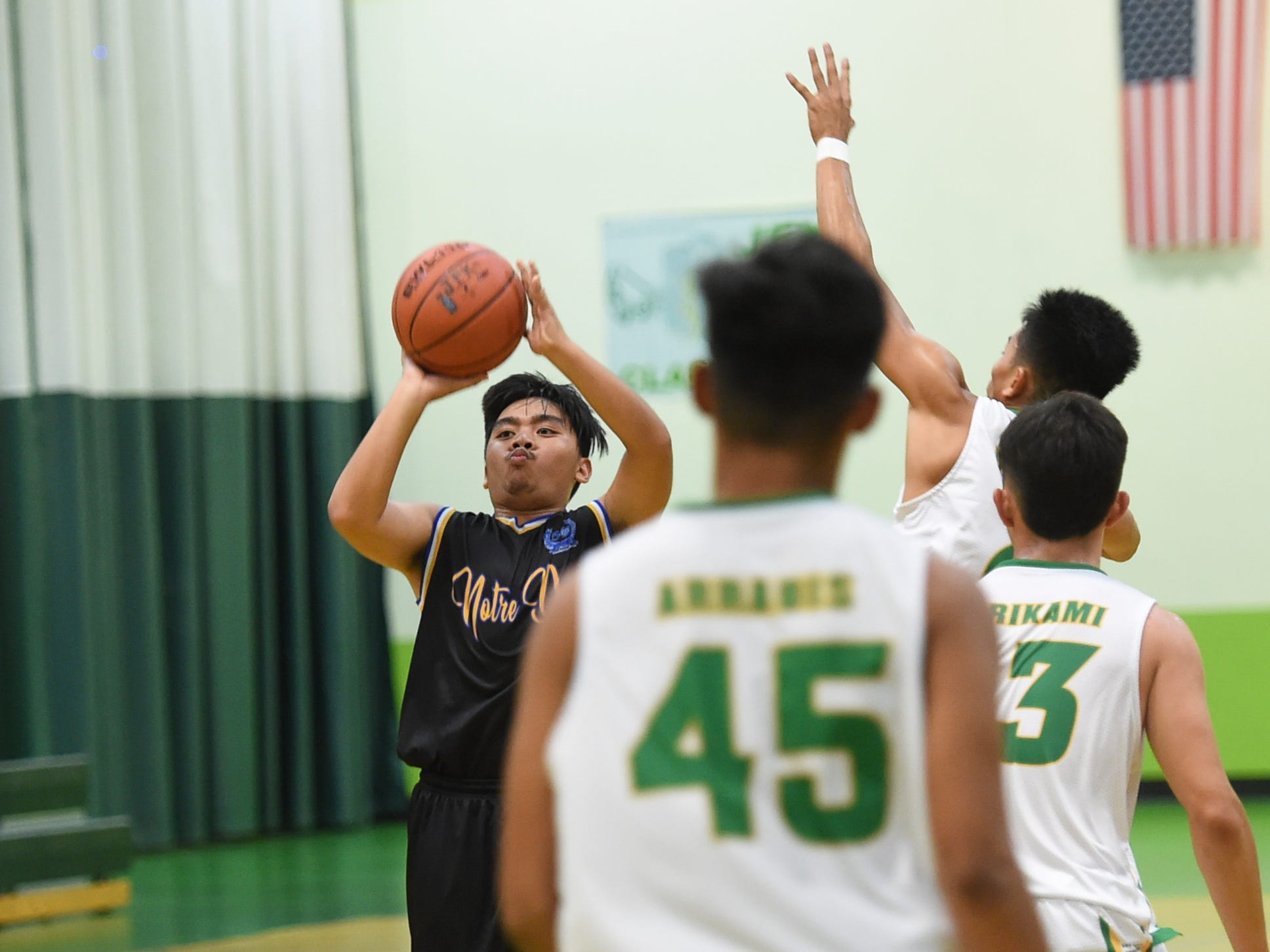 Dean Diras fires from the 3-point line for the Notre Dame Royals during an Independent Interscholastic Athletic Association of Guam Boys' Basketball game at the John F. Kennedy High School Gym, Feb. 2, 2019.