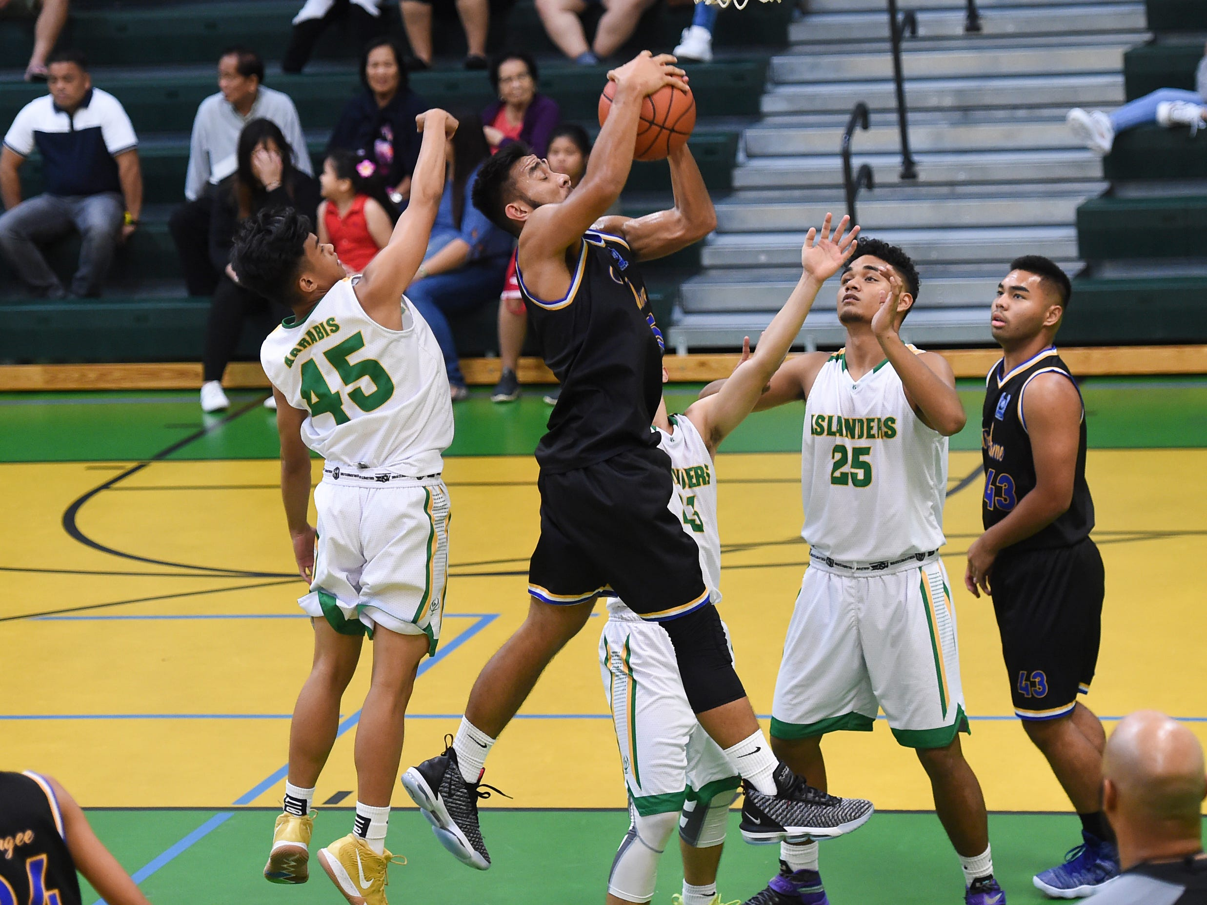 Peter Cruz grabs a rebound for the Notre Dame Royals during an Independent Interscholastic Athletic Association of Guam Boys' Basketball game at the John F. Kennedy High School Gym, Feb. 2, 2019.