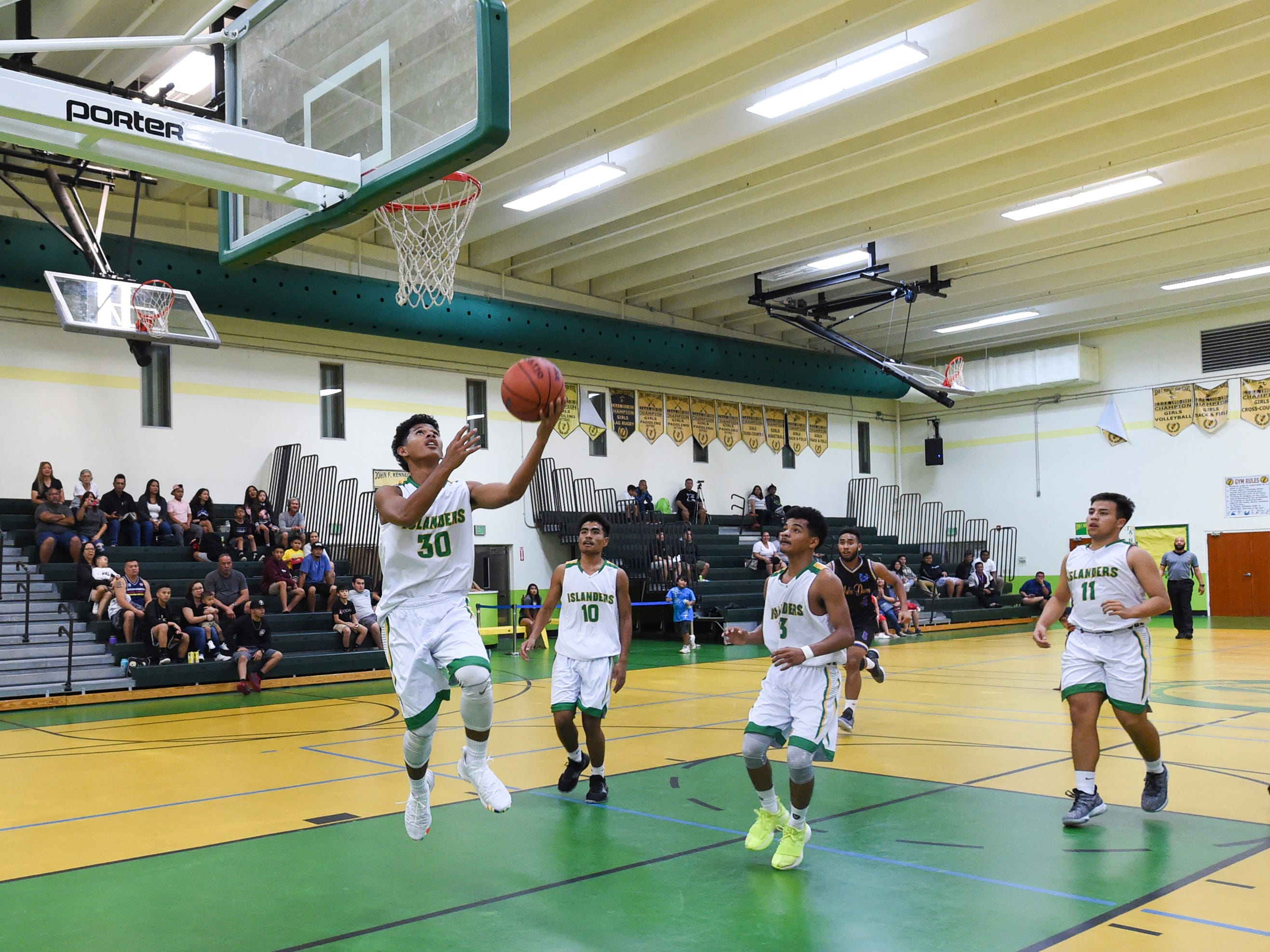John F. Kennedy sophomore Jeremiah Kintoki (30) finishes with a reverse layup during an Independent Interscholastic Athletic Association of Guam Boys' Basketball game at the JFK High School Gym, Feb. 2, 2019.