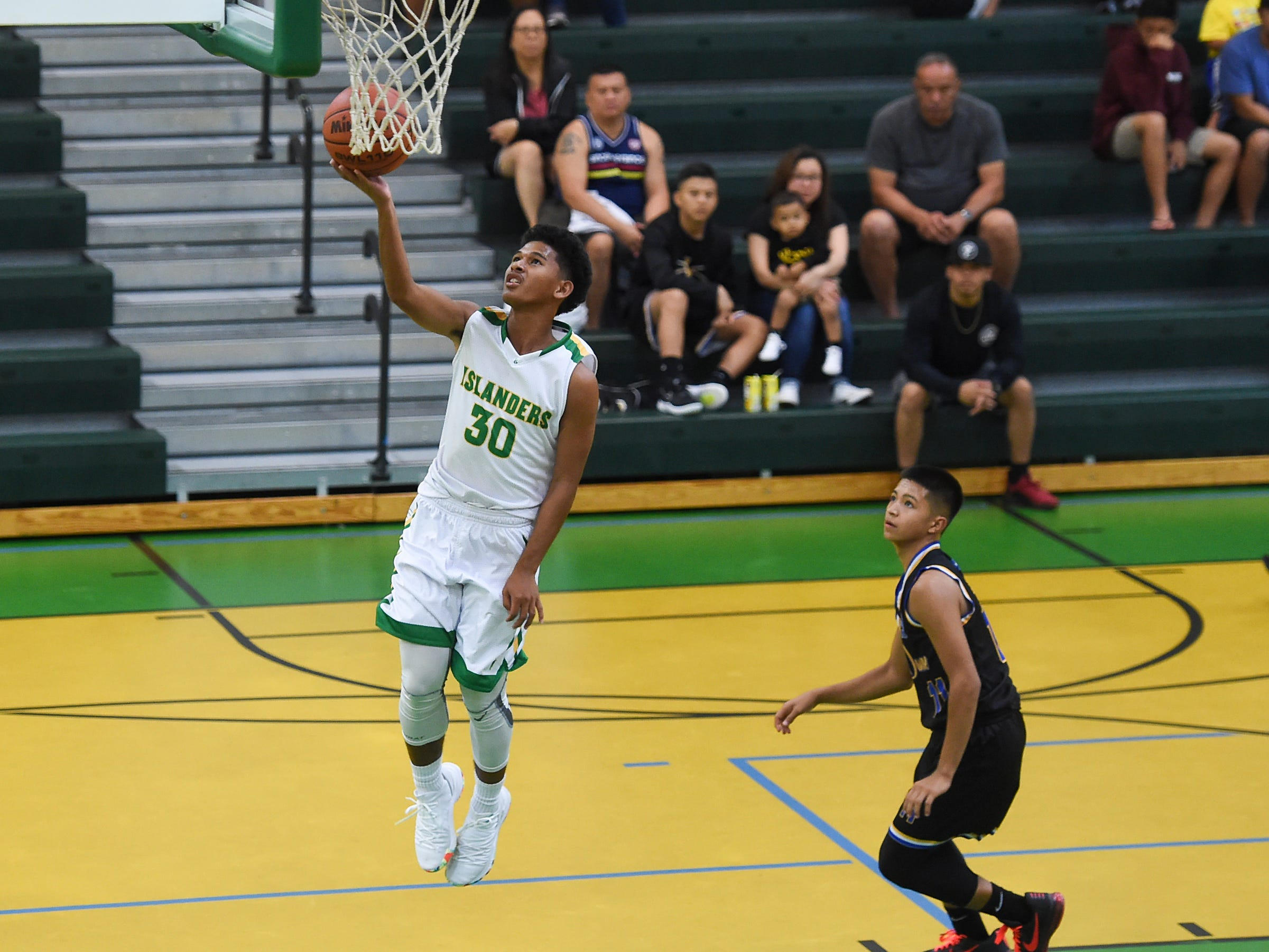 John F. Kennedy's Jeremiah Kintoki (30) scores on a break away layup against the Notre Dame Royals during their Independent Interscholastic Athletic Association of Guam Boys' Basketball game at the JFK High School Gym, Feb. 2, 2019.