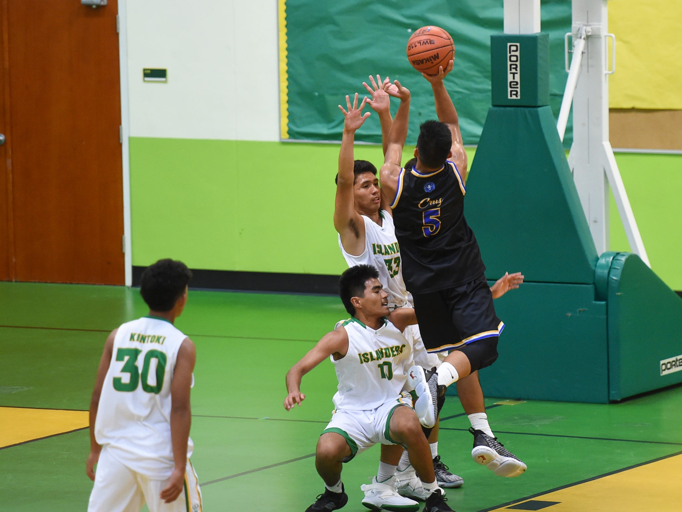 Notre Dame player Peter Cruz (5) is fouled on a drive by the John F. Kennedy Islanders during their Independent Interscholastic Athletic Association of Guam Boys' Basketball game at the JFK High School Gym, Feb. 2, 2019.