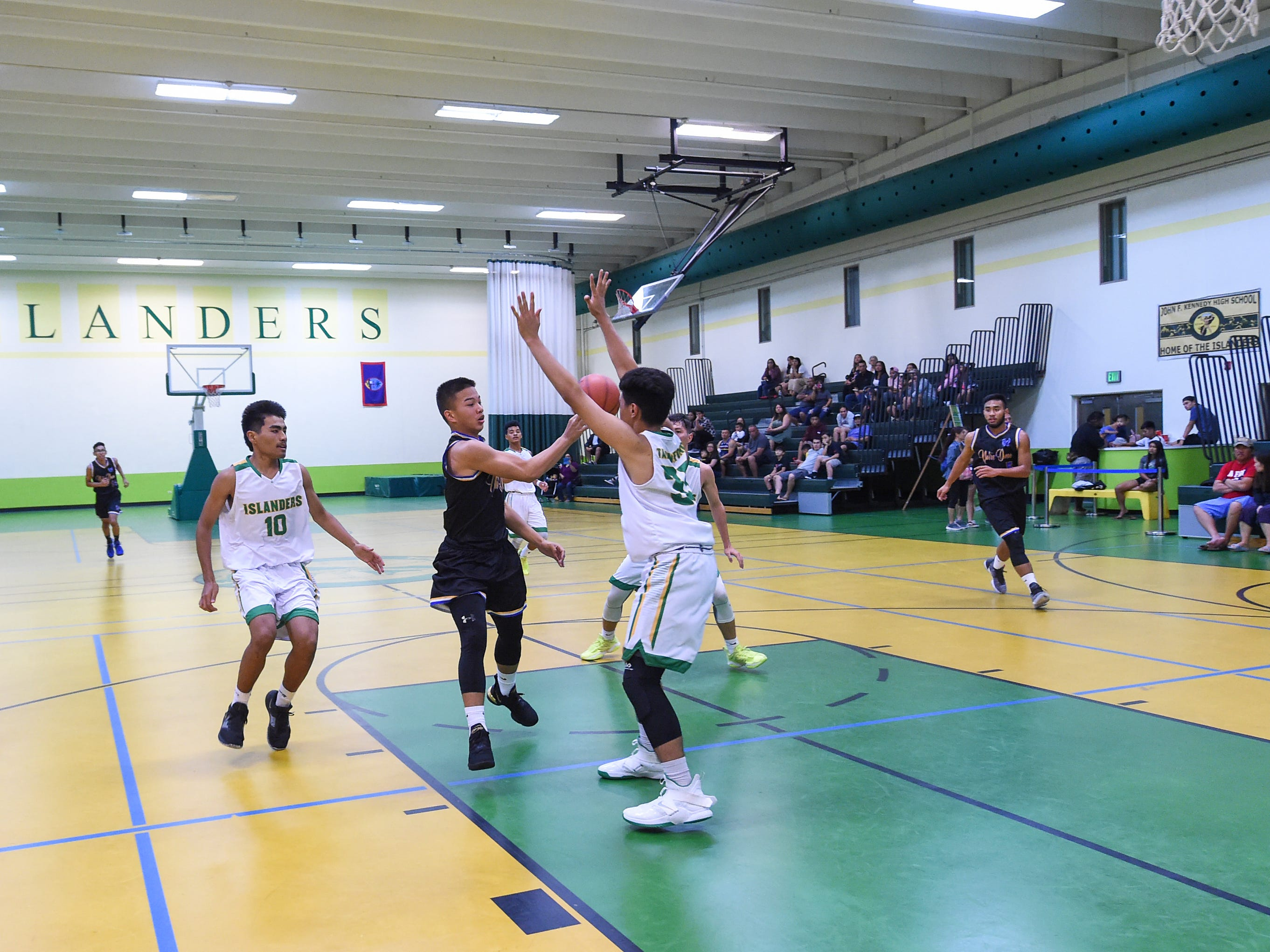 Notre Dame's Nolan Sablan attempts to deliver a no-look pass against the John F. Kennedy Islanders during their Independent Interscholastic Athletic Association of Guam Boys' Basketball game at the JFK High School Gym, Feb. 2, 2019.
