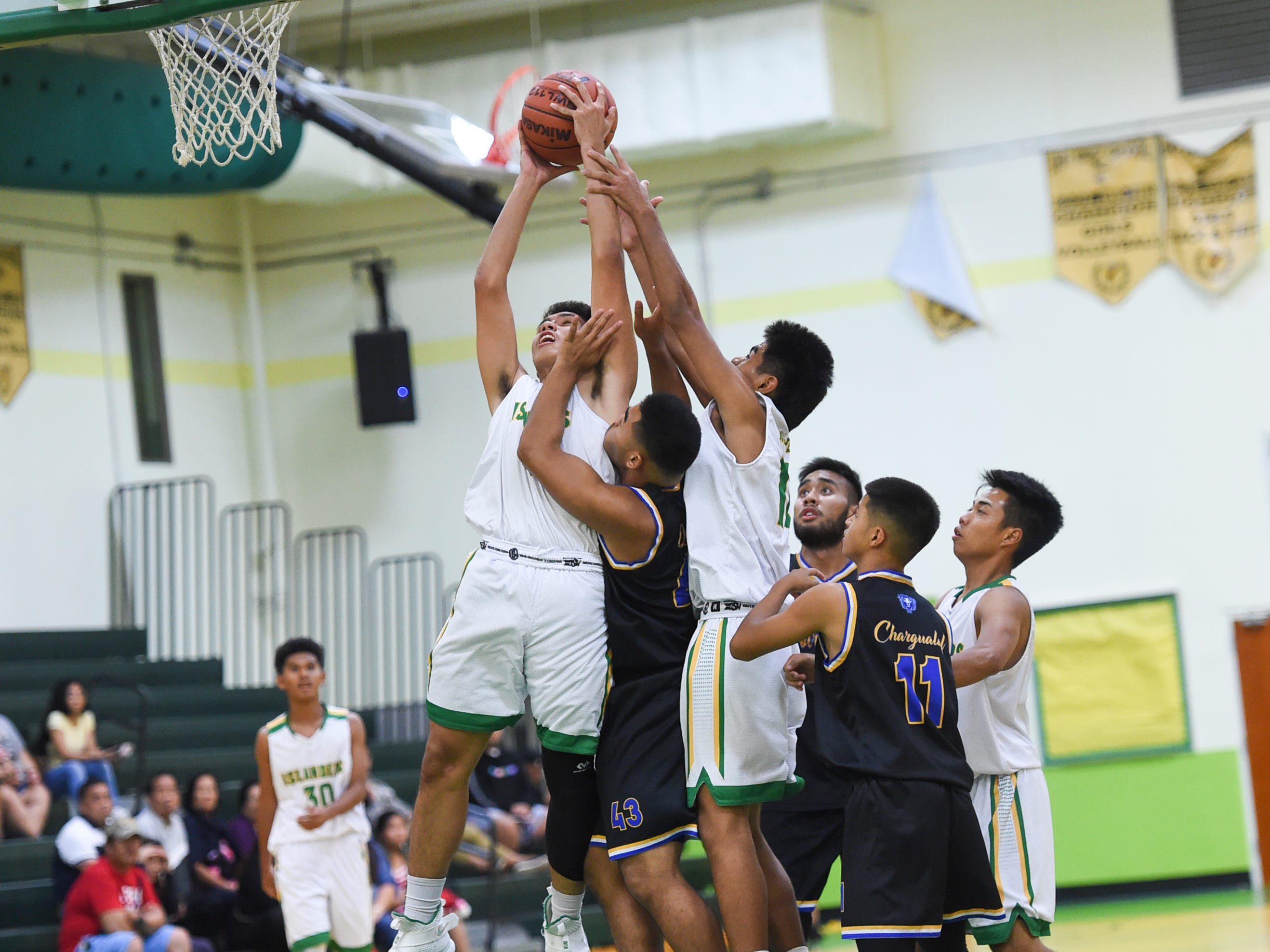 Notre Dame Royals and John F. Kennedy Islanders players battle for a rebound during their Independent Interscholastic Athletic Association of Guam Boys' Basketball game at the JFK High School Gym, Feb. 2, 2019.
