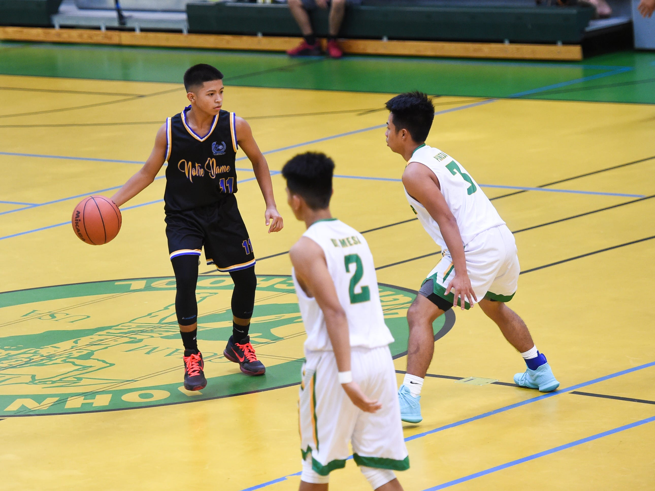 Notre Dame Royal Bryce Chargualaf (11) handles the ball during an Independent Interscholastic Athletic Association of Guam Boys' Basketball game at the John F. Kennedy High School Gym, Feb. 2, 2019.