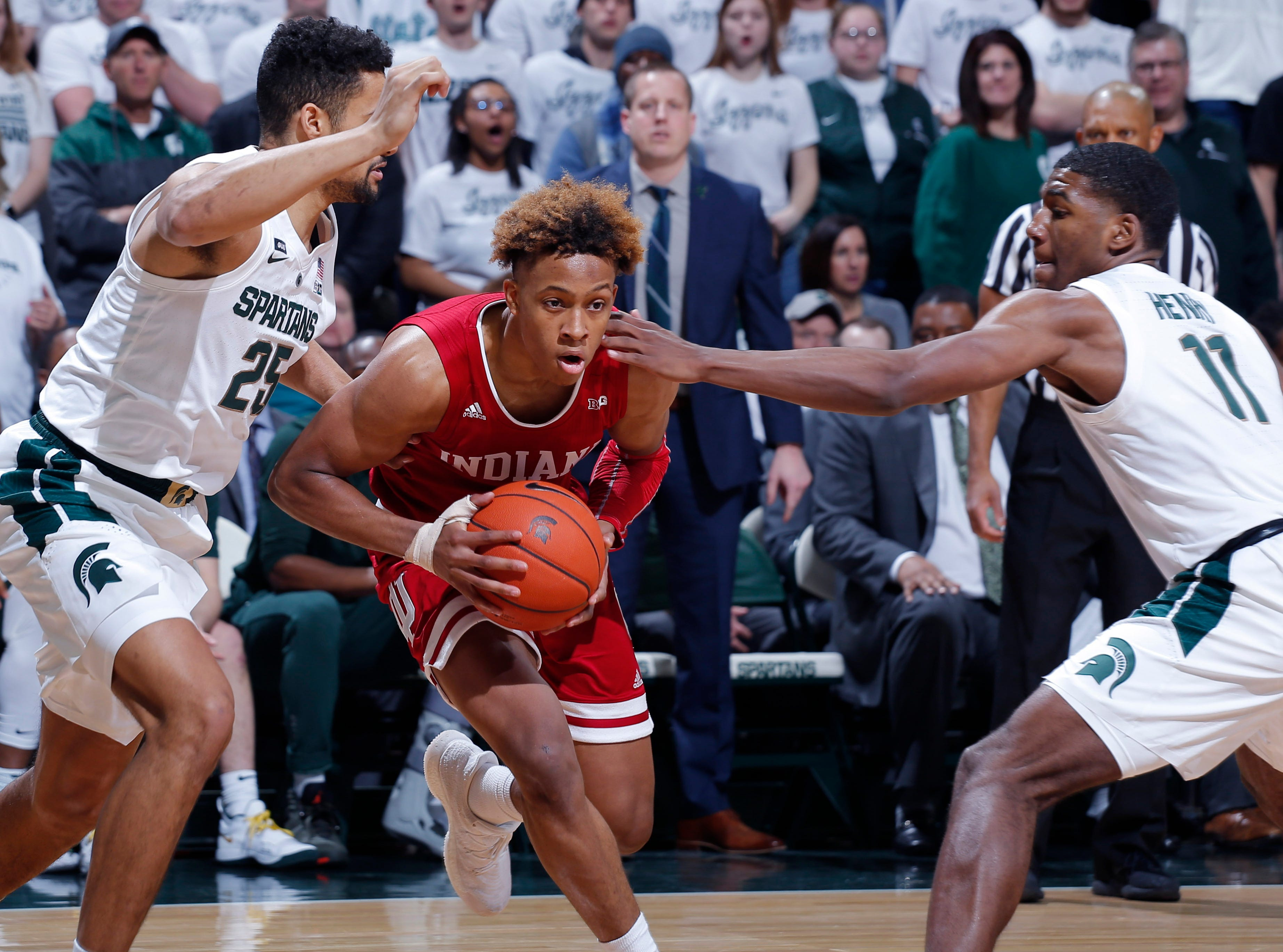 Indiana's Romeo Langford, center, drives between Michigan State's Kenny Goins, left, and Aaron Henry (11) during the first half of an NCAA college basketball game, Saturday, Feb. 2, 2019, in East Lansing, Mich.