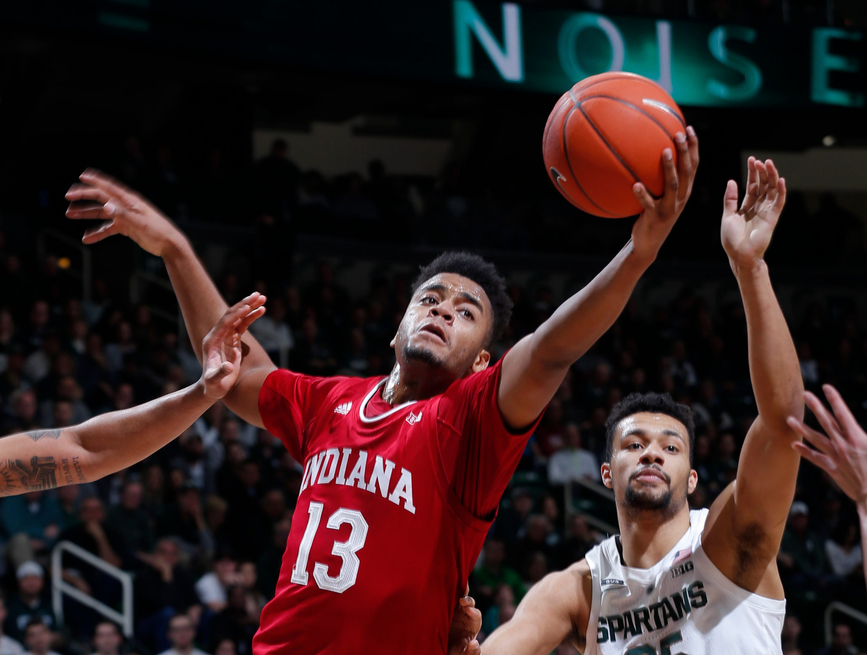 Indiana's Juwan Morgan (13) and Michigan State's Kenny Goins reach for a rebound during the first half of an NCAA college basketball game, Saturday, Feb. 2, 2019, in East Lansing, Mich.