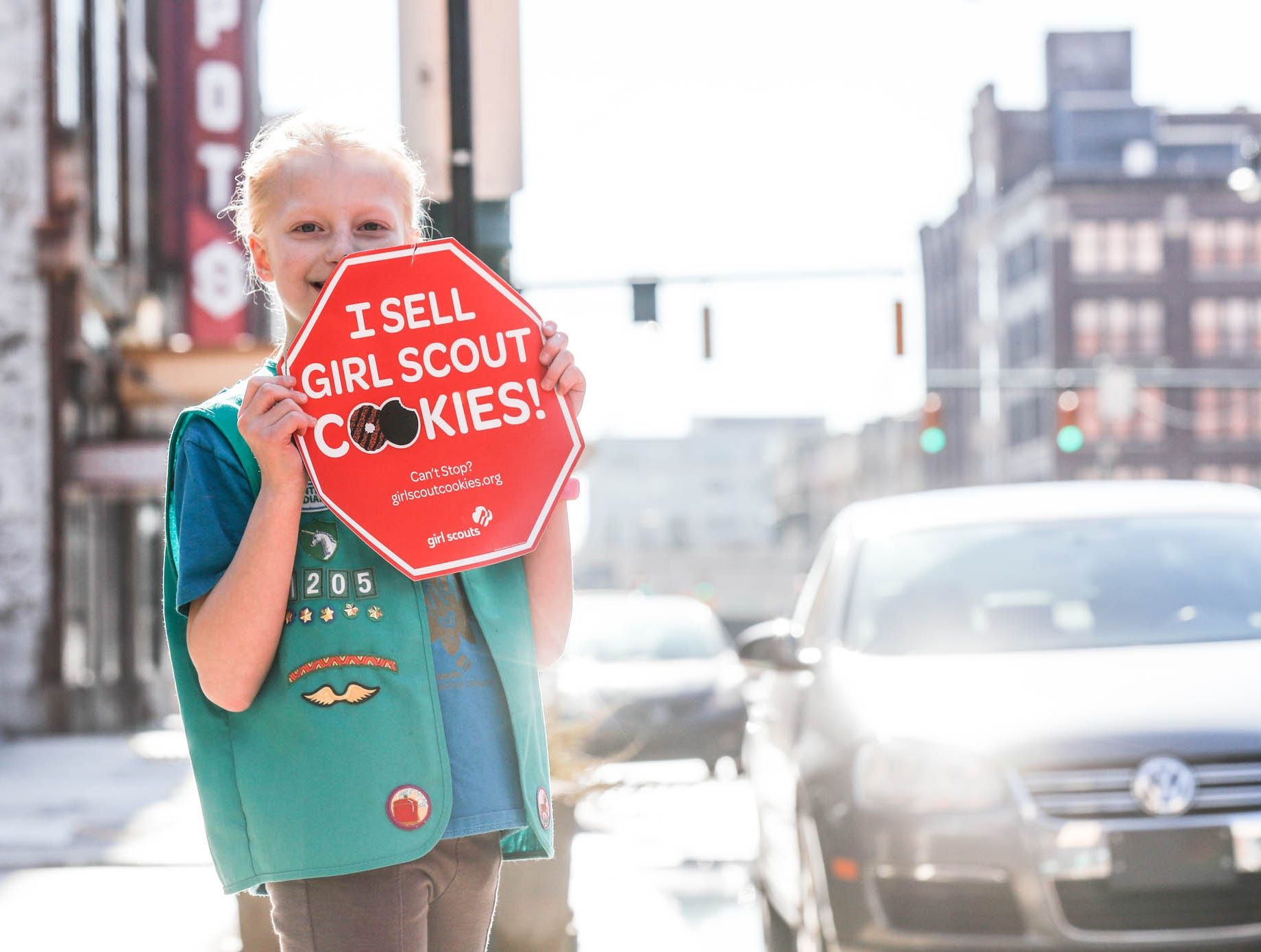 Hailey Gill, from troop 1205 dances with her Girl Scout cookie sales sign along S. Meridian St., on a near sixty-degree afternoon in Indianapolis on Sunday, Feb. 3, 2019.