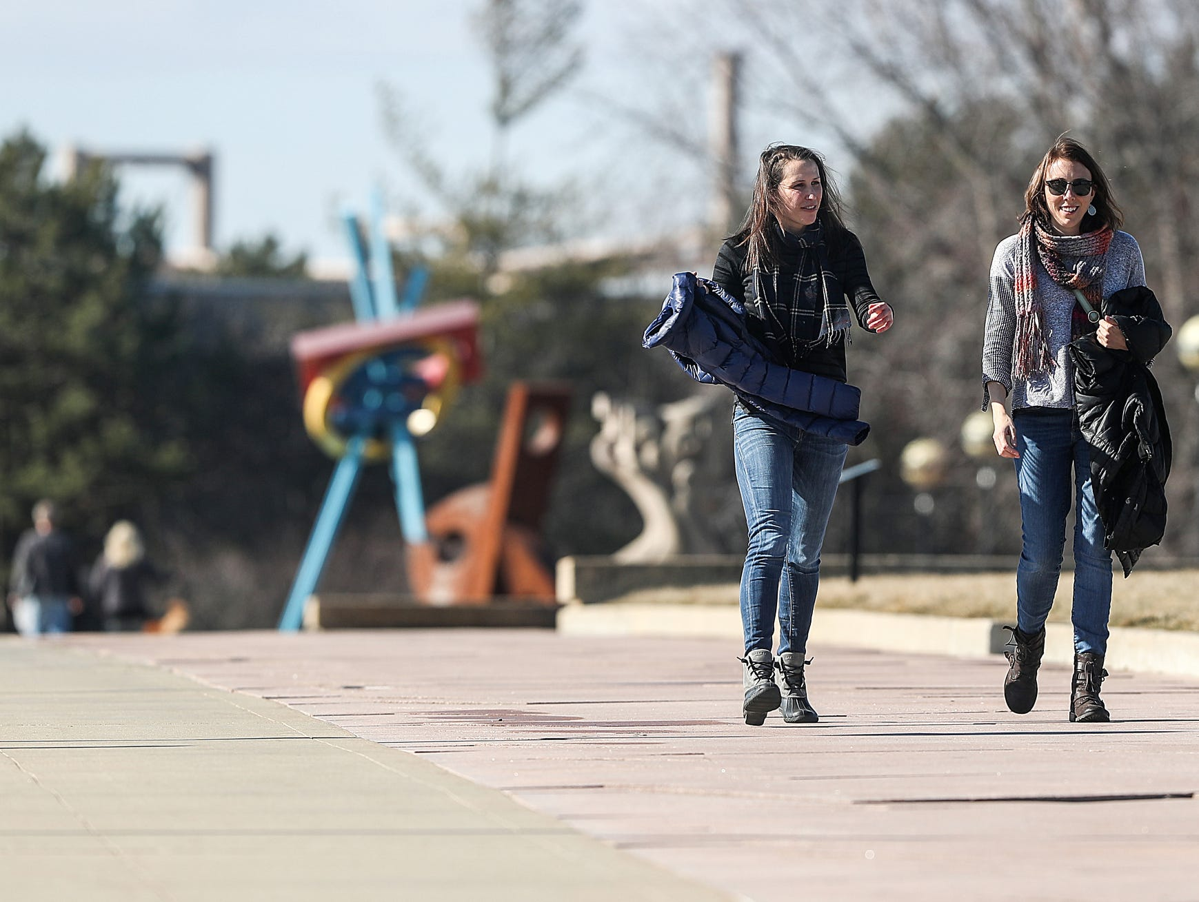 From left, Calah Schlabach and Emily Arkus take their coats off for a 65-degree walk at White River State Park in Indianapolis, Sunday, Feb. 3, 2019. The warm weather comes just days after sub-zero temperatures swept over Indiana.